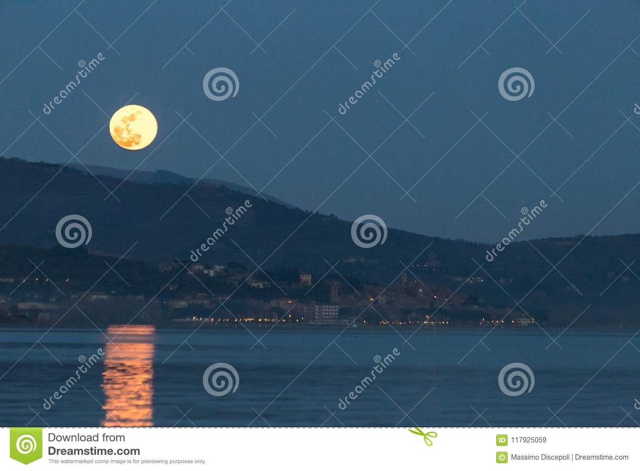 Beautiful view of full moon just over Passignano Umbria, refle