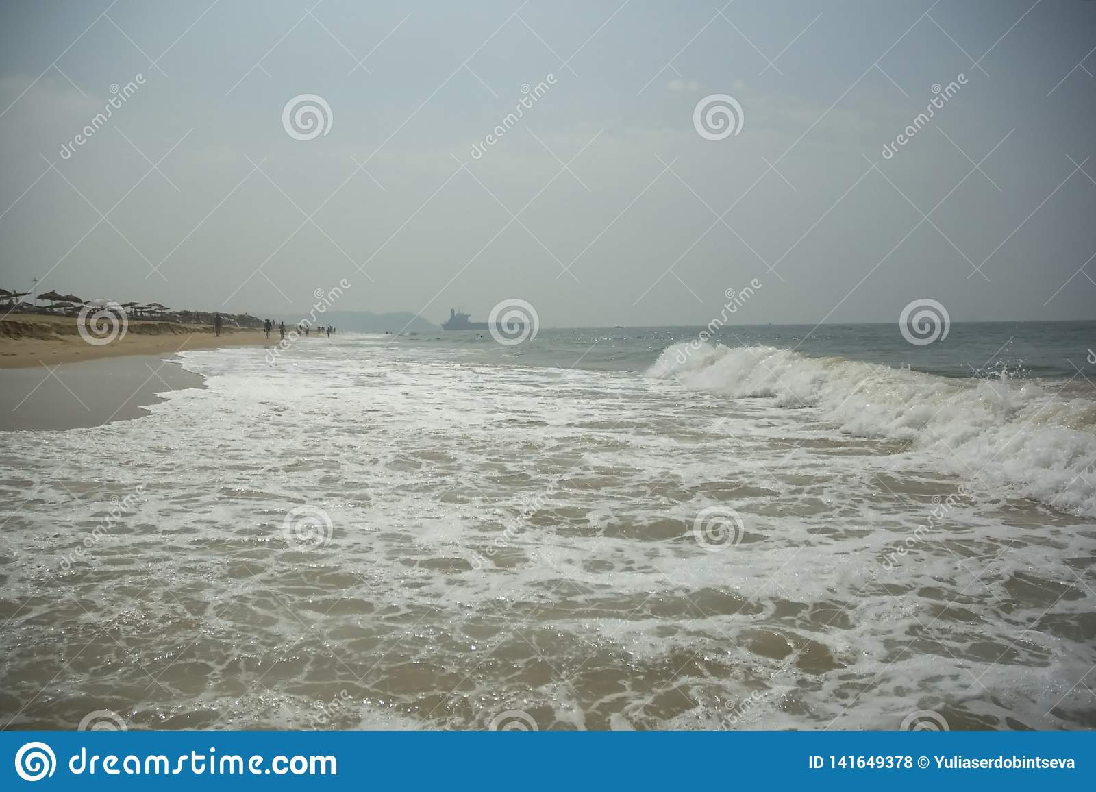 Beautiful view of a huge beach and waves and an old ship stranded