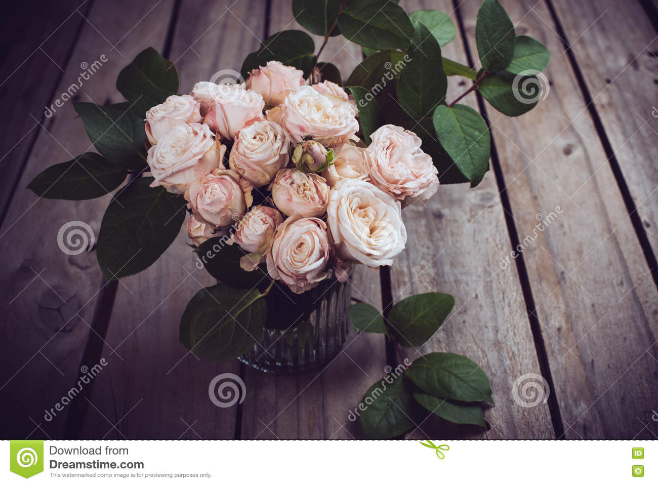 Beautiful vintage bouquet of fresh roses on wooden board