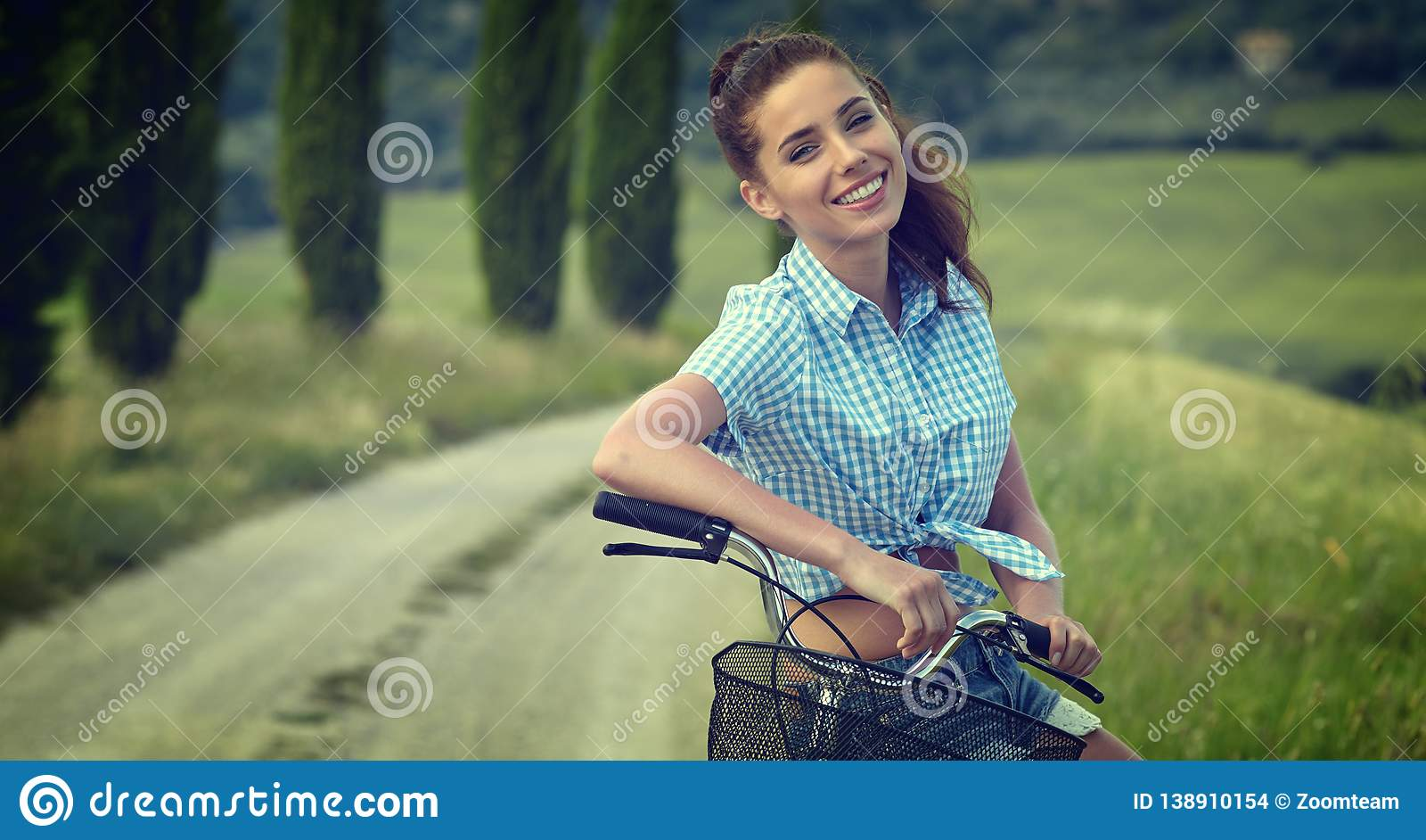 Beautiful vintage girl sitting next to bike, summer time