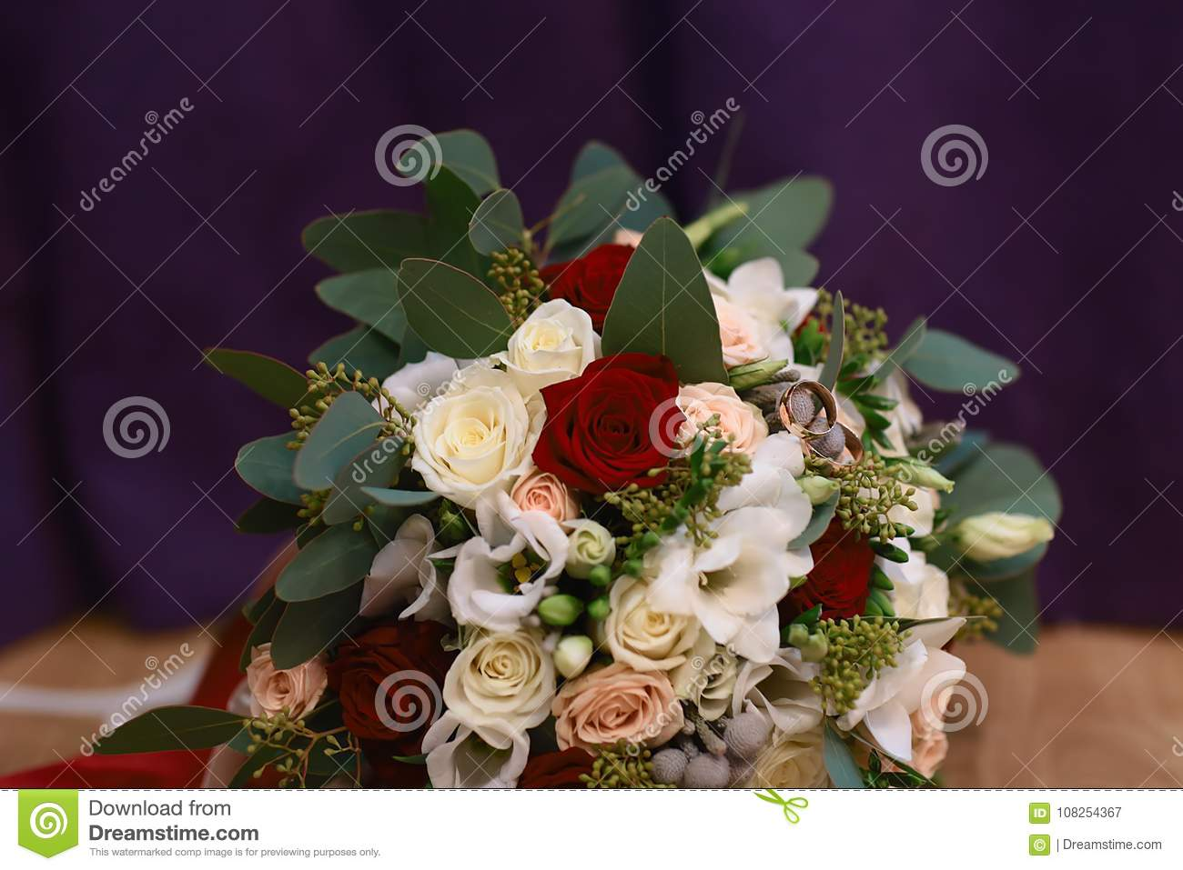 Beautiful Wedding Bouquet With And Gold Wedding Rings With A Ribbon