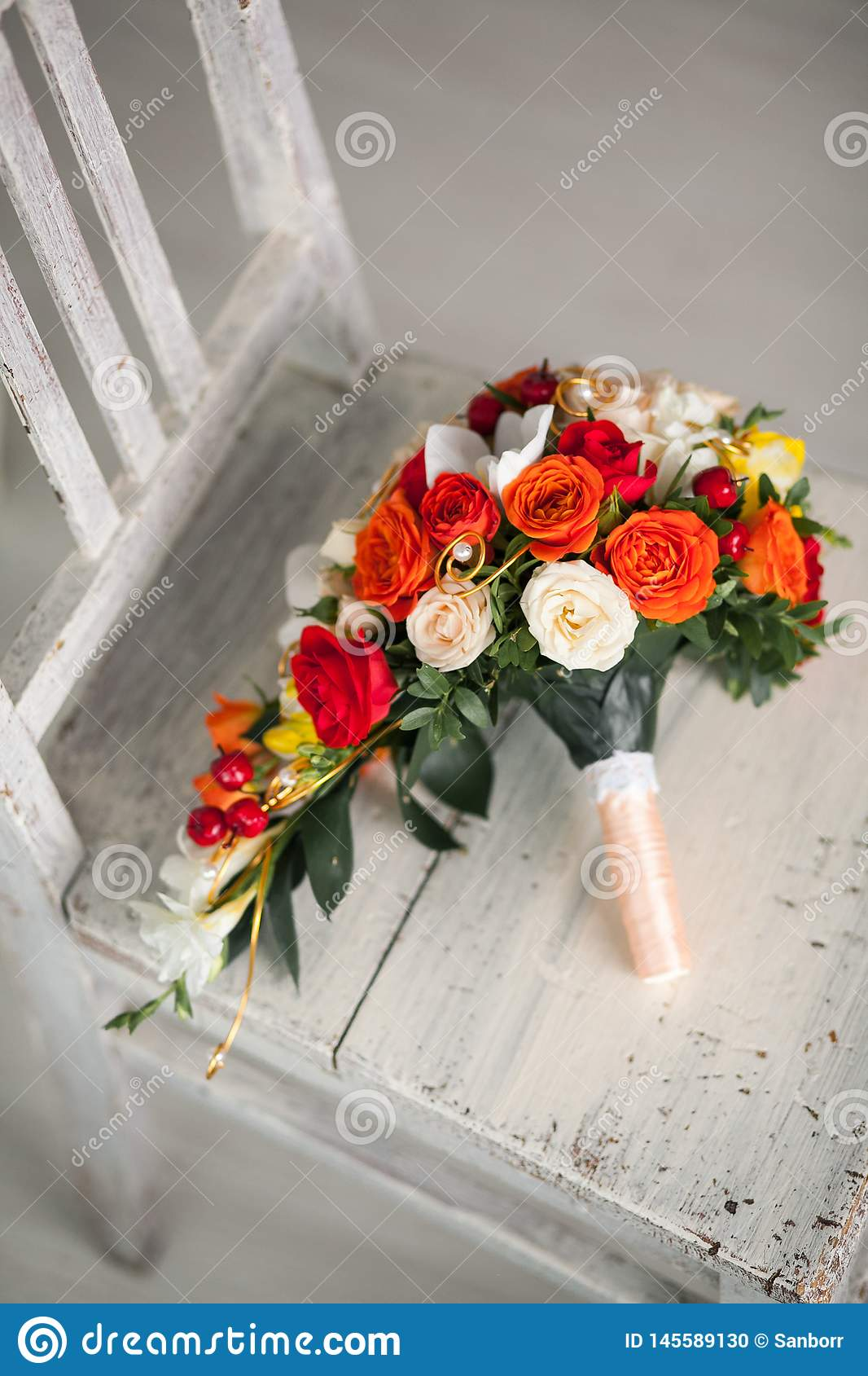 Beautiful wedding bouquet on an old worn wooden chair, close-up. The bride`s bouquet of white, orange and red roses, tied with a
