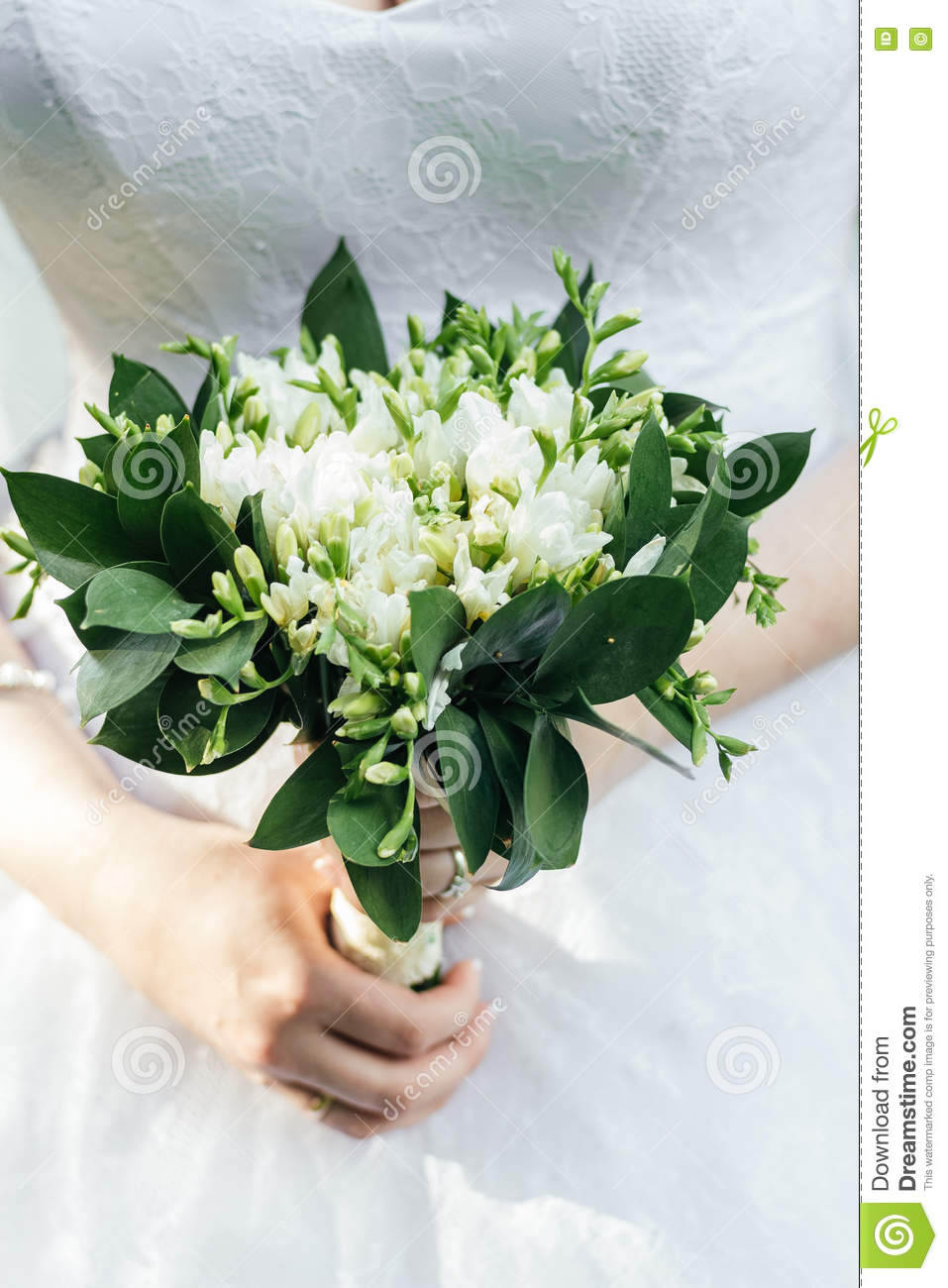 Beautiful wedding bouquet of white freesia flowers in brides hand royalty free stock photo izmirmasajfo Gallery