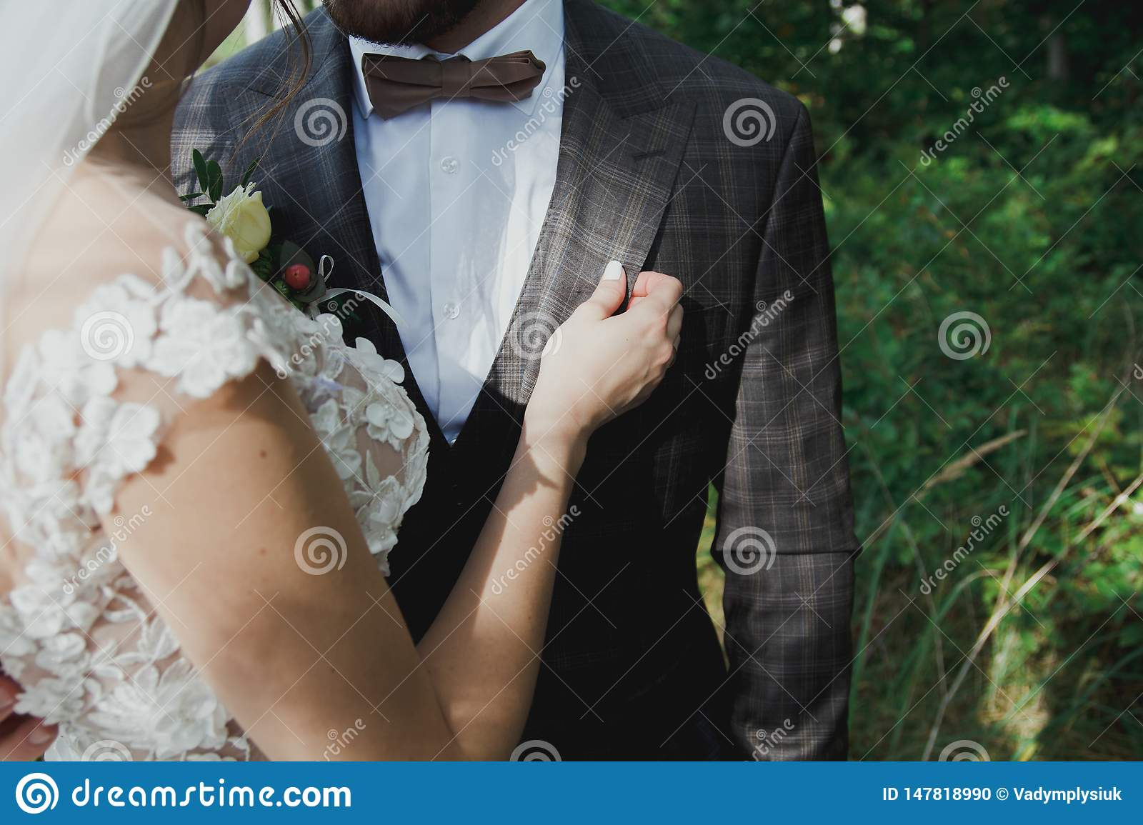 Beautiful wedding couple in the forest. The bride touches the groom in bow tie tenderly. Wedding buttonhole and checkered suit in