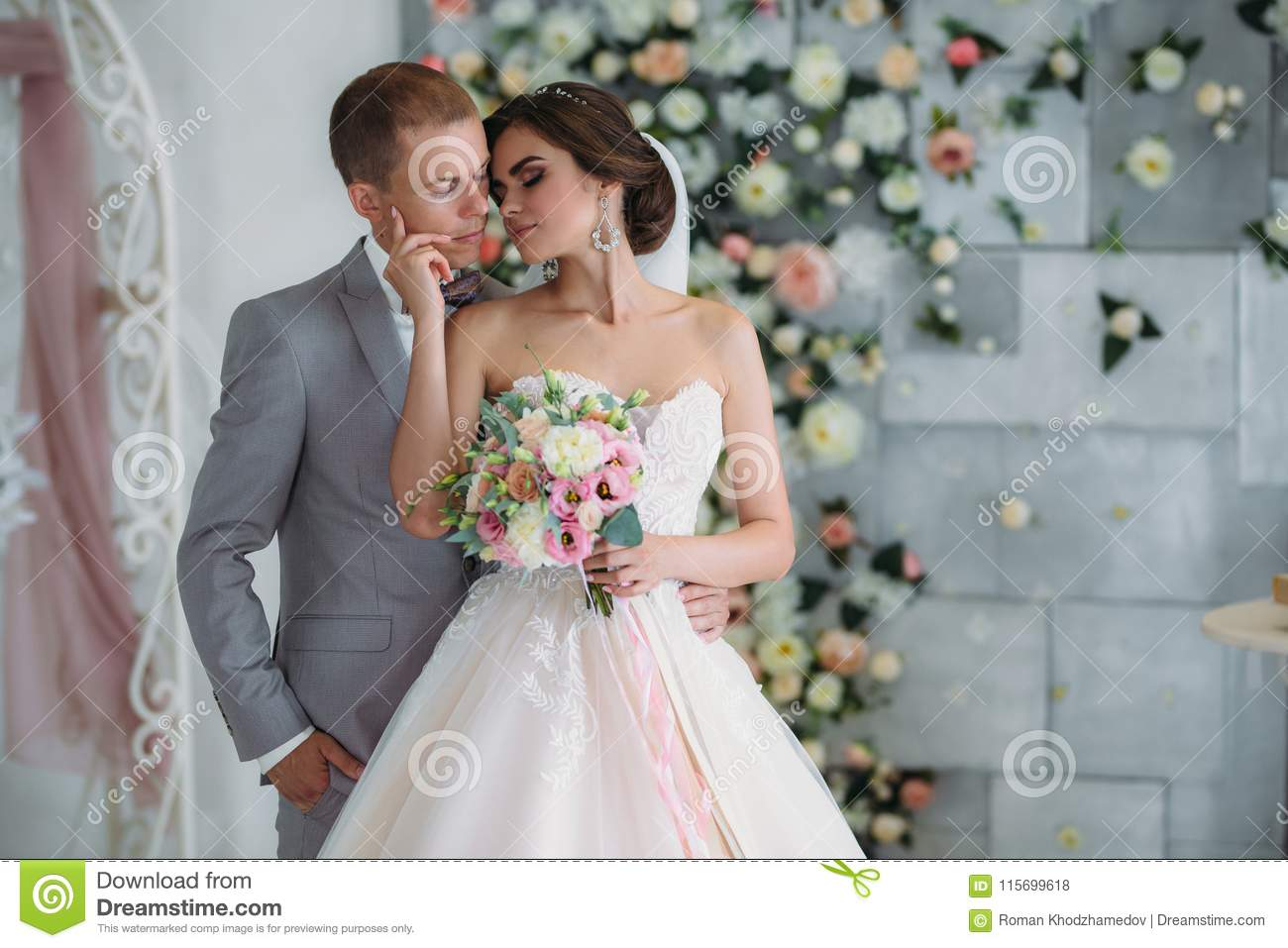 Beautiful wedding couple hugging in bright studio. The groom in a business gray suit, a white shirt in a bow tie and a