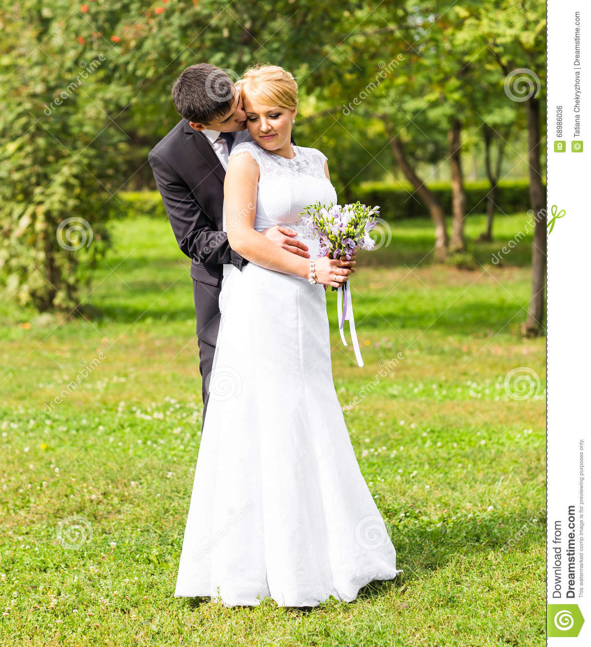 Beautiful wedding couple outdoors. They kiss and hug each other