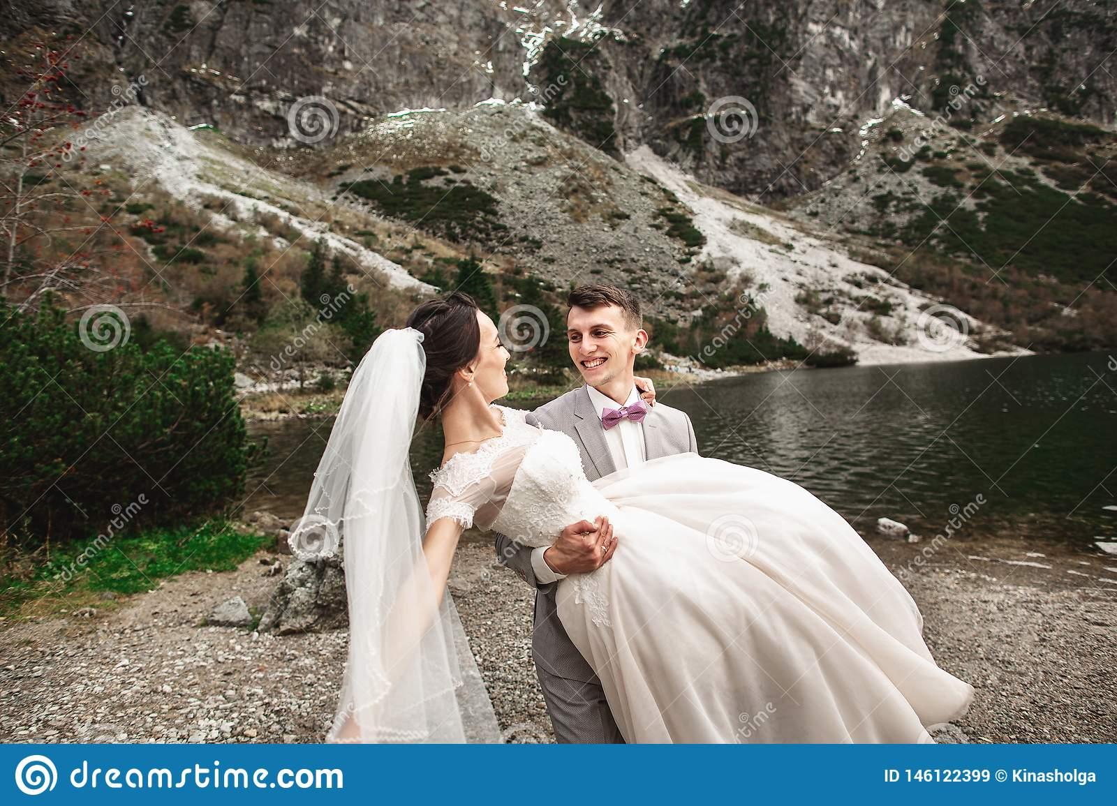 Beautiful wedding photosession. The groom circles his young bride, on the shore of the lake Morskie Oko. Poland