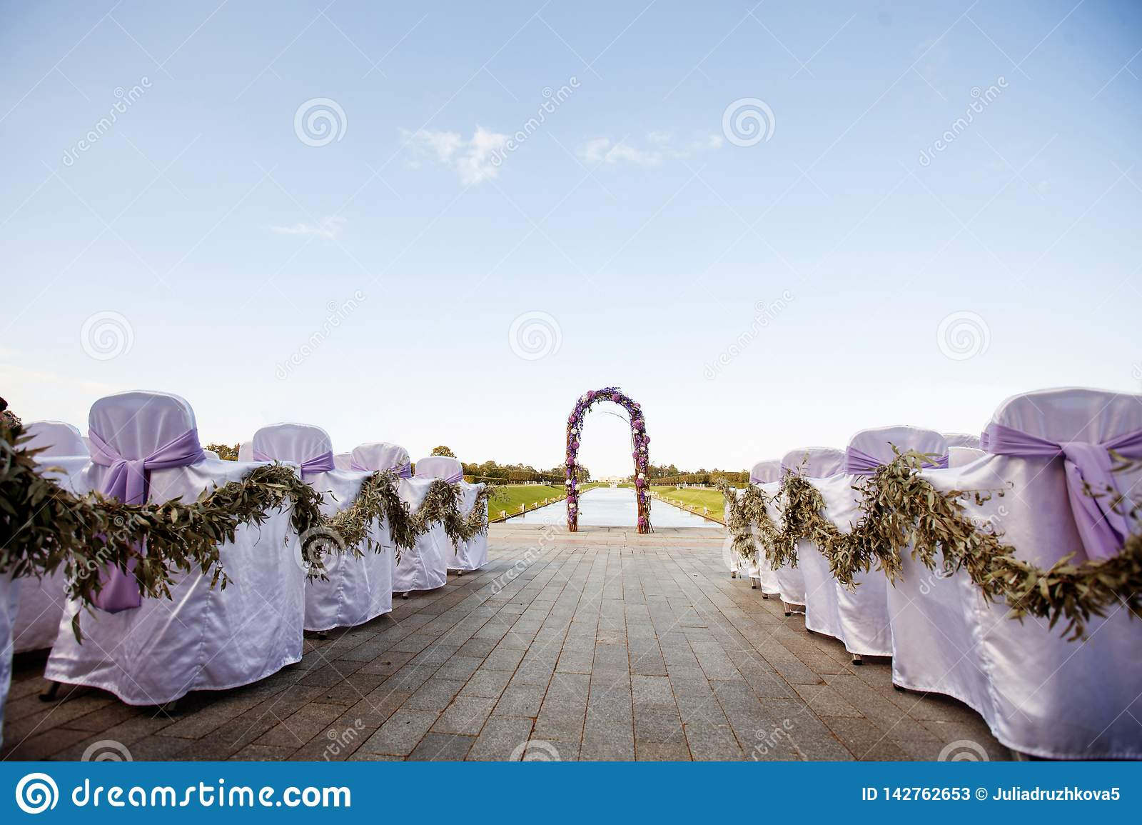 Beautiful wedding. The round arch is decorated with flowers and greenery, the ceremony on the seashore. Guest chairs are decorated