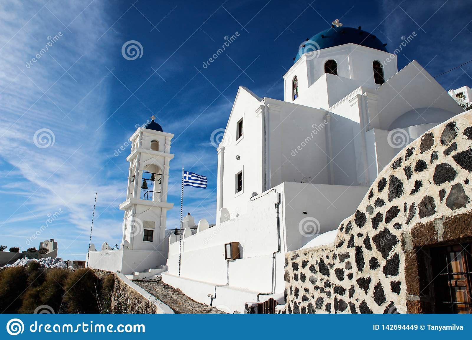 Beautiful white church with blue domes and the Greek flag on the island