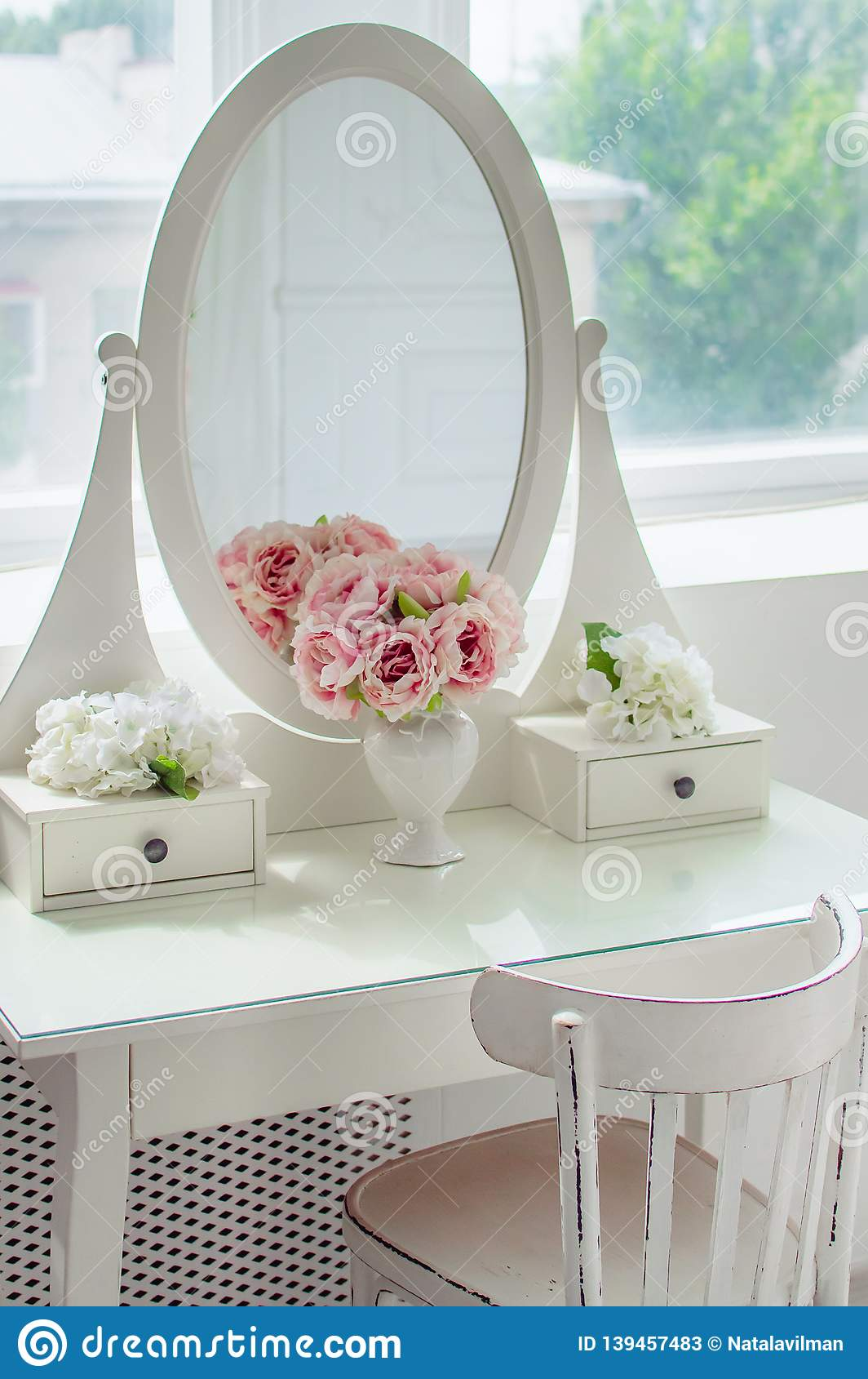 A beautiful white mirror on the table. Elegant bright interior