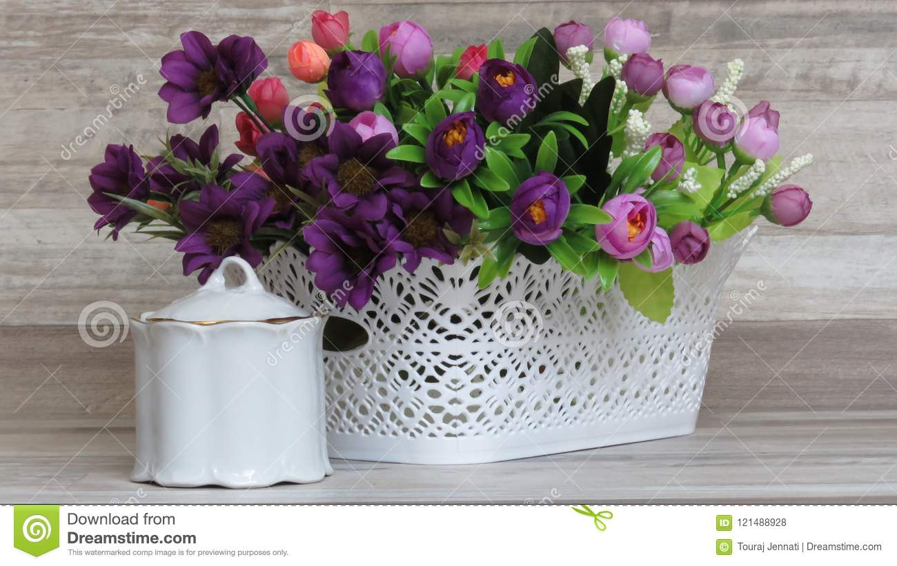 Beautiful White Plastic Basket And Artificial Flowers Stock Photo