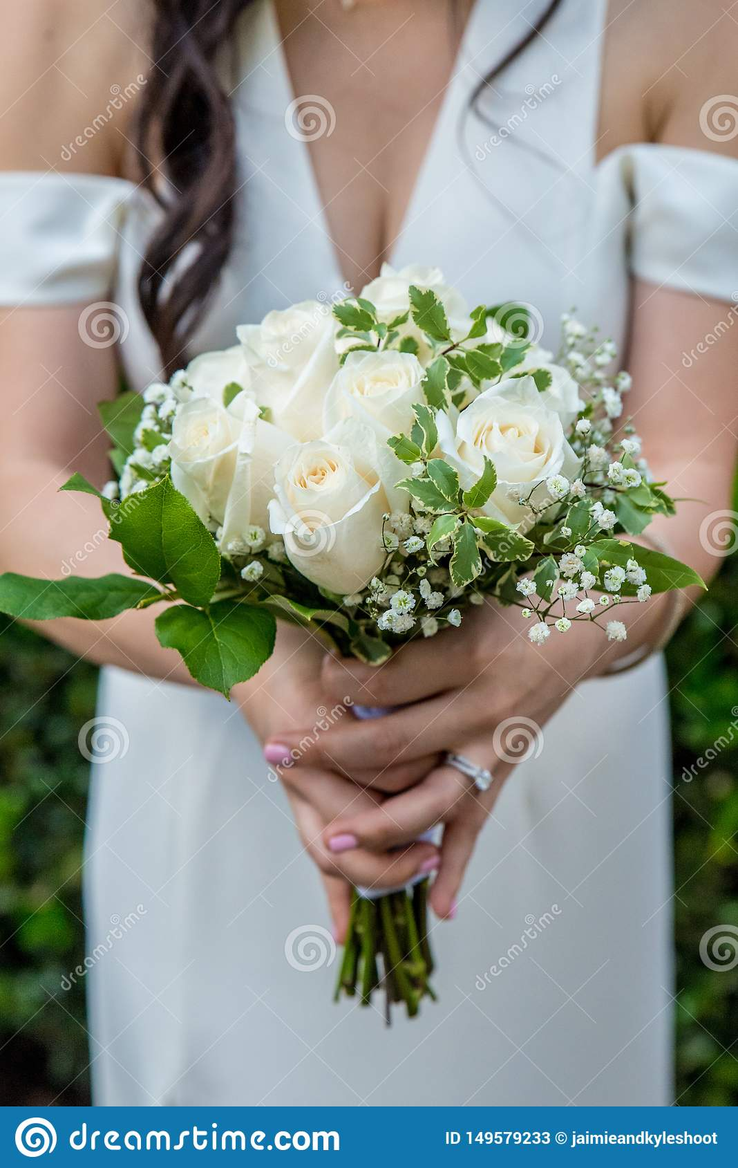 Beautiful white rose bouquet with baby`s breath held by a bride with dark hair wearing a white wedding dress and an engagement rin