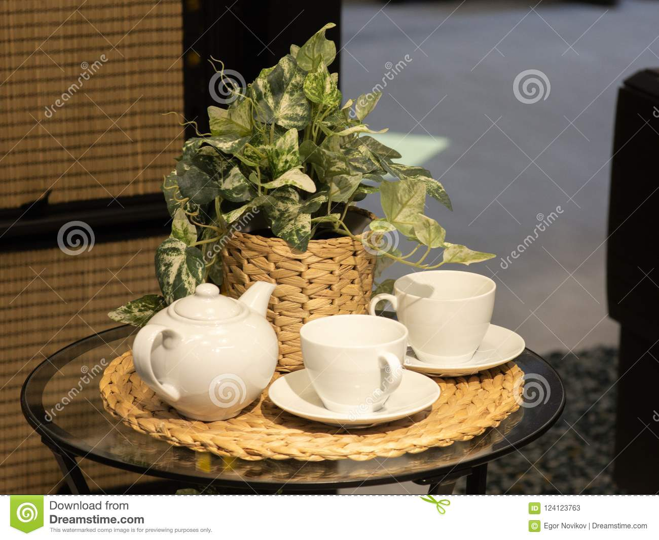A beautiful white set of two bowls and a teapot, in the background a flower