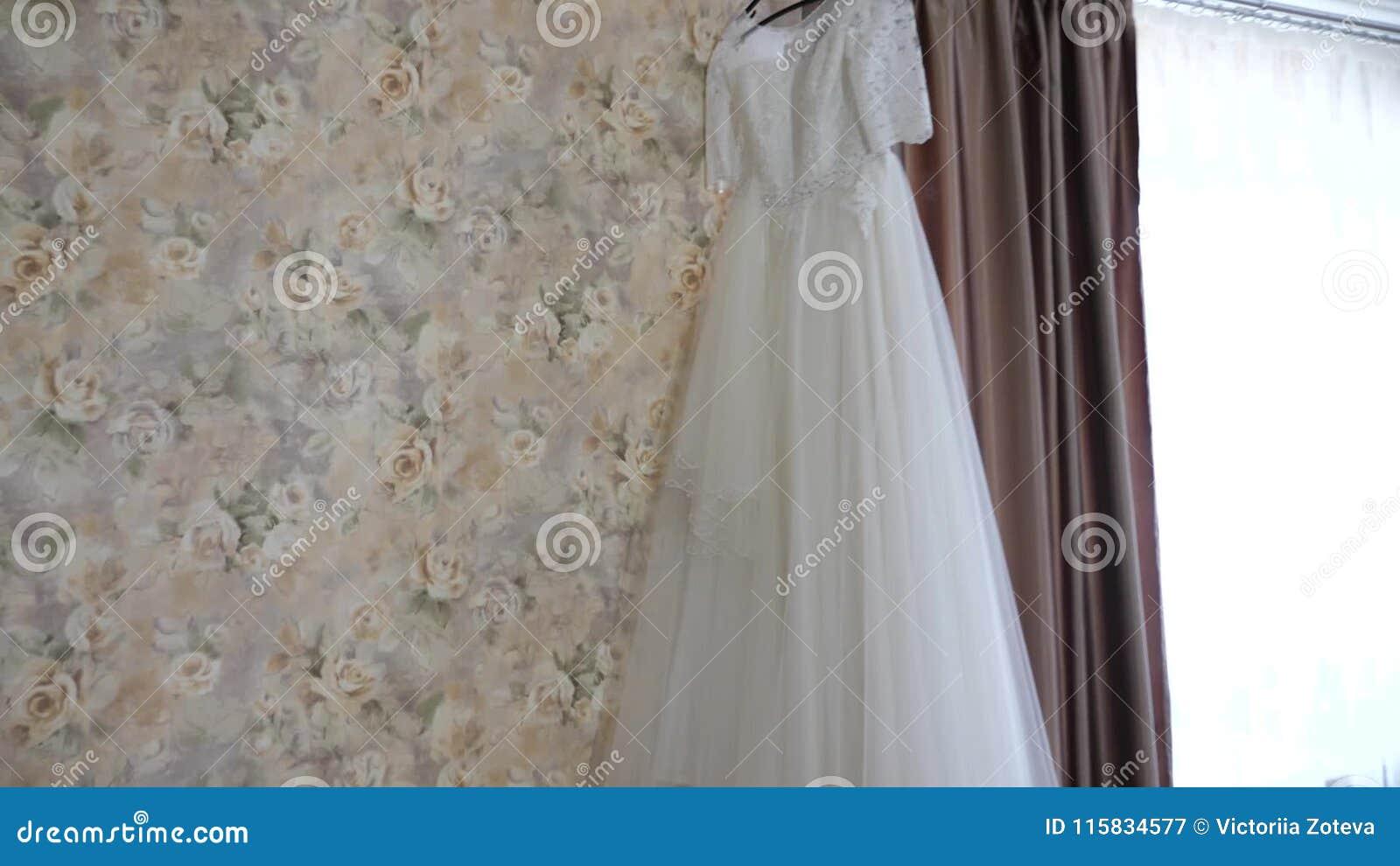 Beautiful White Wedding Dress Hanging On Hanger At The Window Stock ...