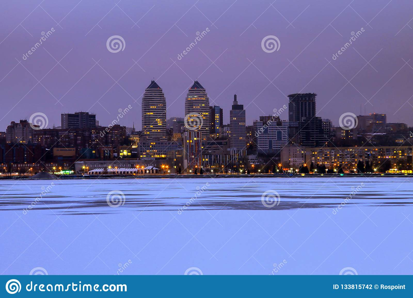 Beautiful winter view of the Dnepr city in the evening, the ice of the frozen Dnieper river is covered with fresh snow.