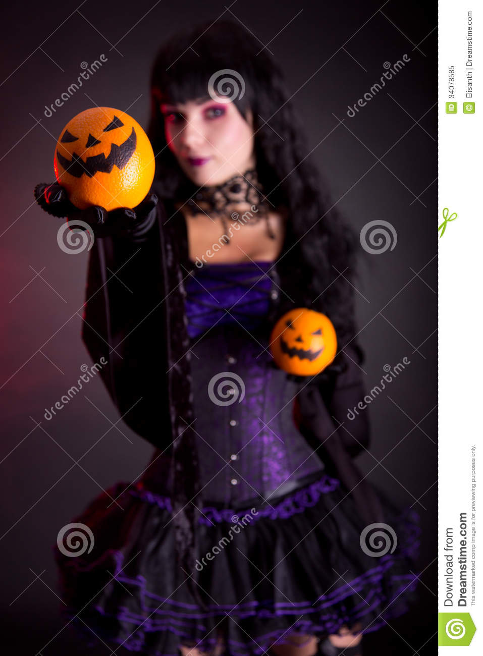 Beautiful witch in purple gothic Halloween costume