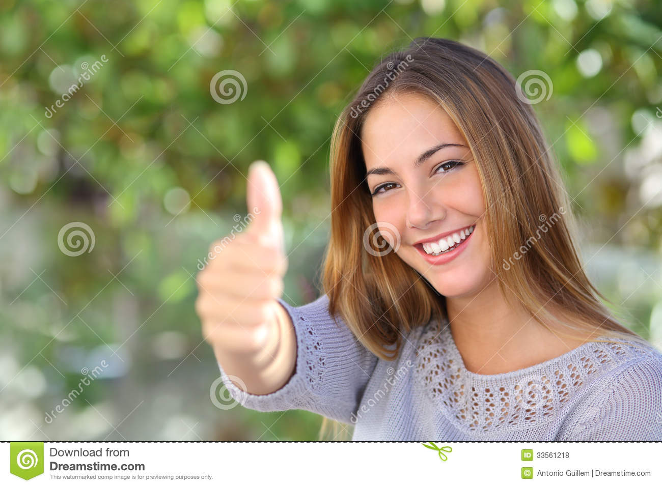Beautiful woman agreement with thumb up outdoor