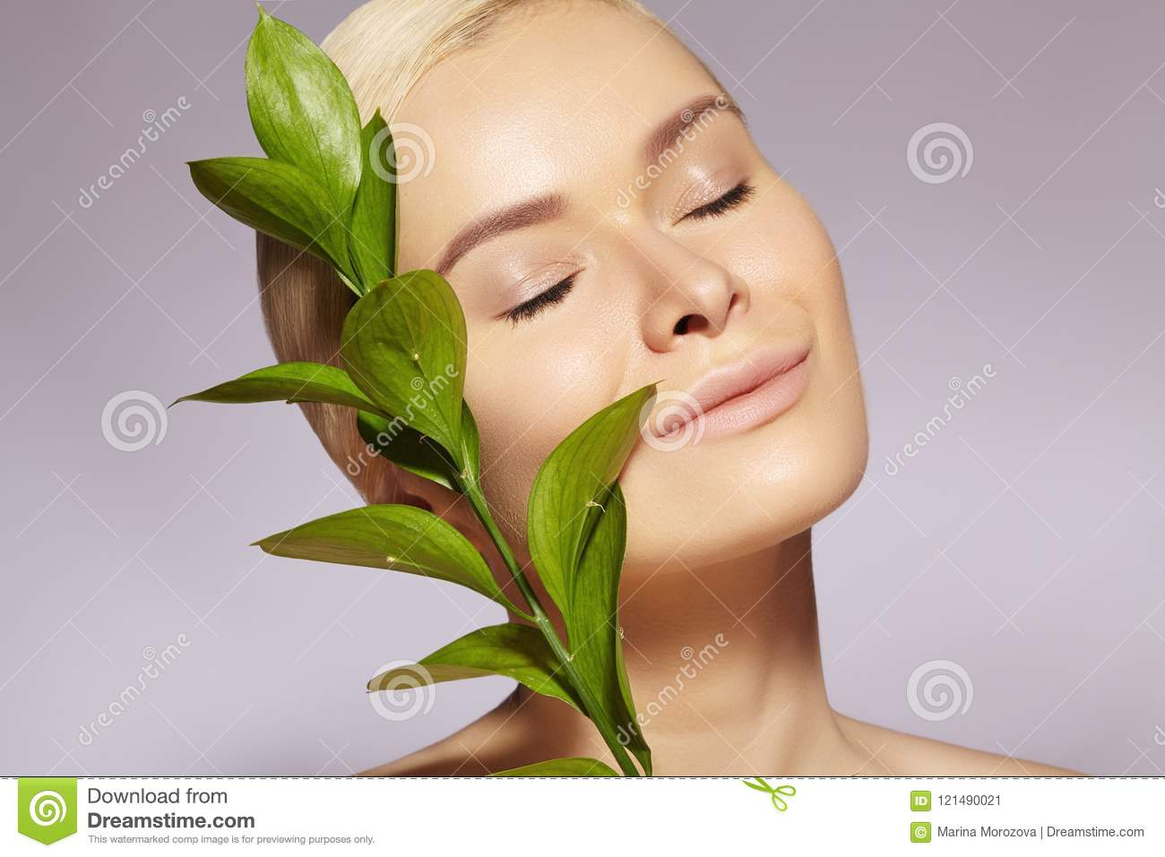 Beautiful Woman applies Organic Cosmetic. Spa and Wellness. Model with Clean Skin. Healthcare. Picture with Leaf