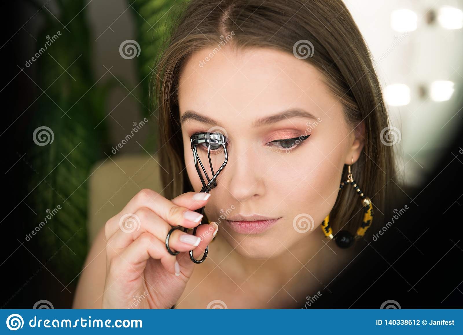 Beautiful woman apply fake eyelashes and doing evening makeup