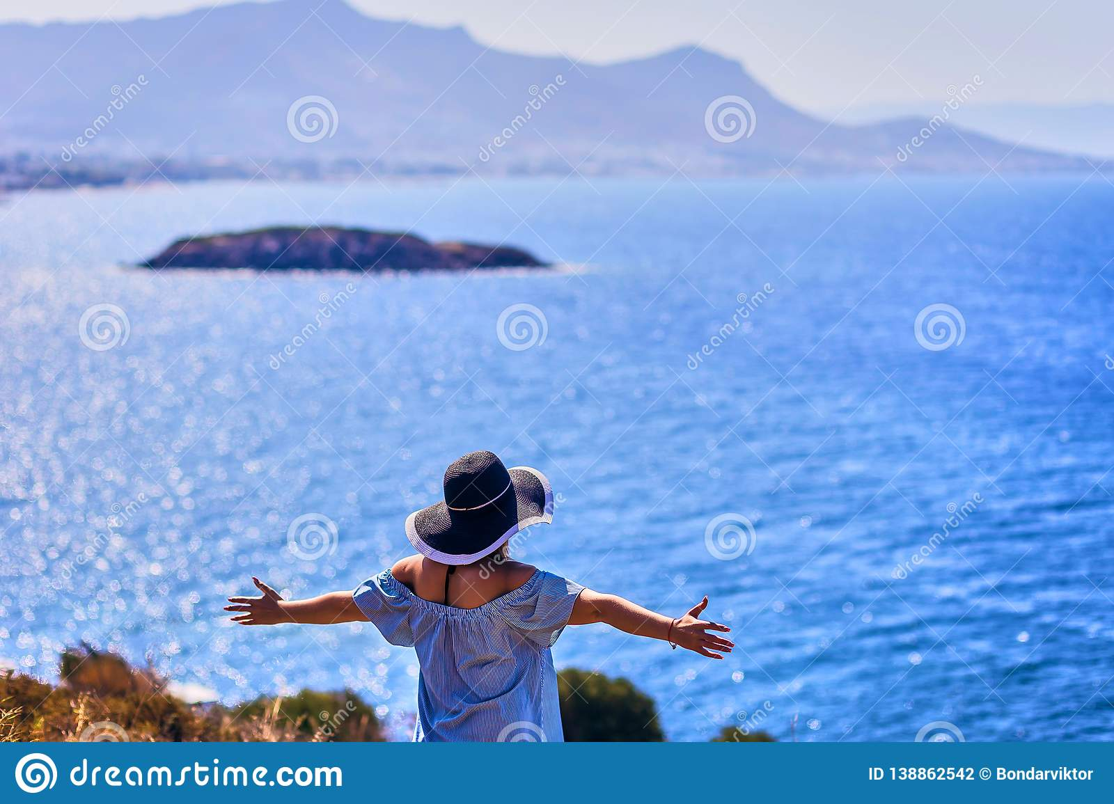 Beautiful woman in beach hat enjoying sea view with blue sky at sunny day in Bodrum, Turkey. Vacation Outdoors Seascape Summer