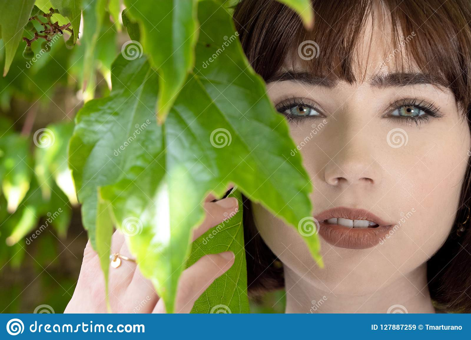 Beautiful woman behind green leaves looking at camera