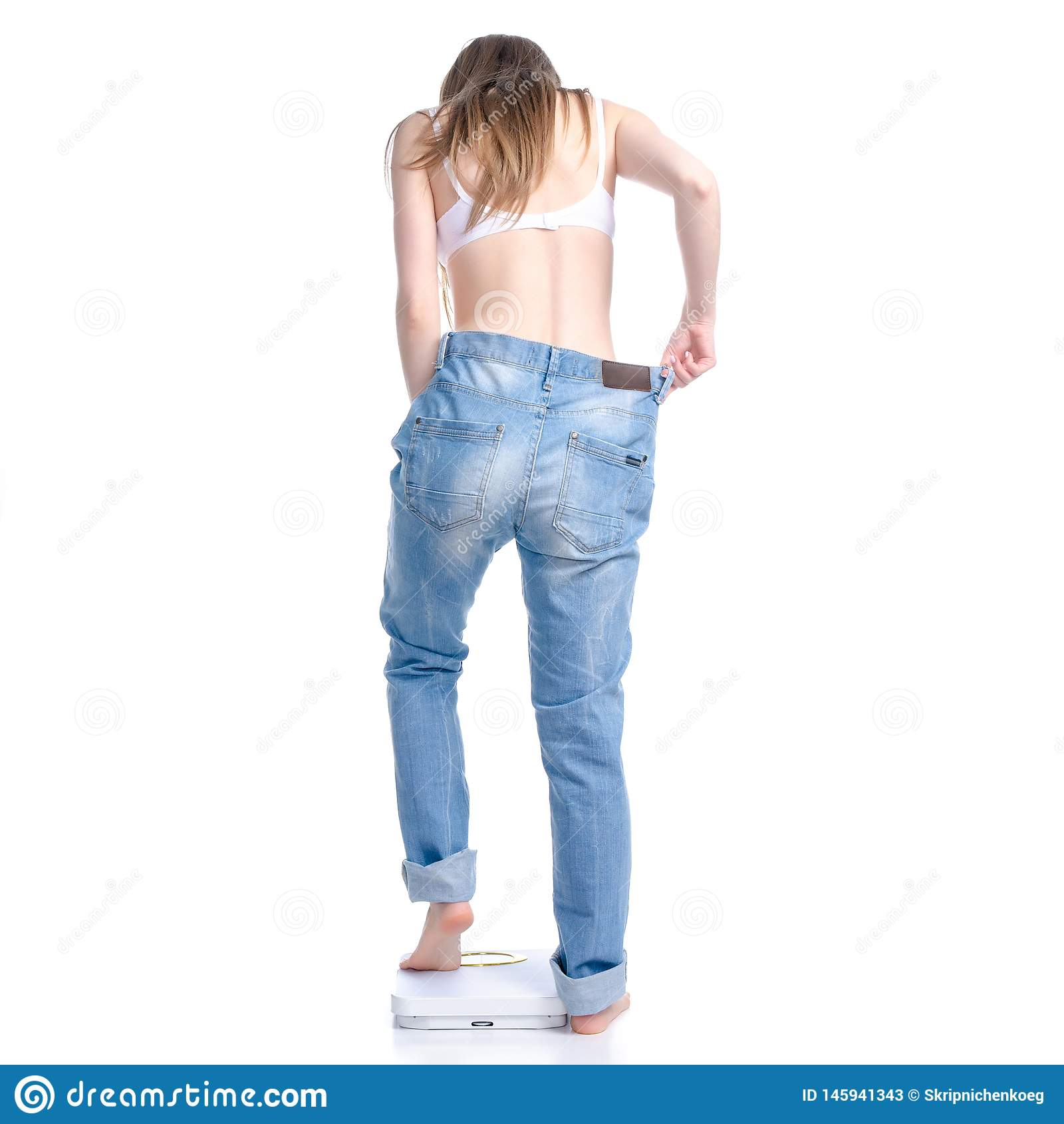 Beautiful woman in big jeans on weighing-machine, weight loss slimming