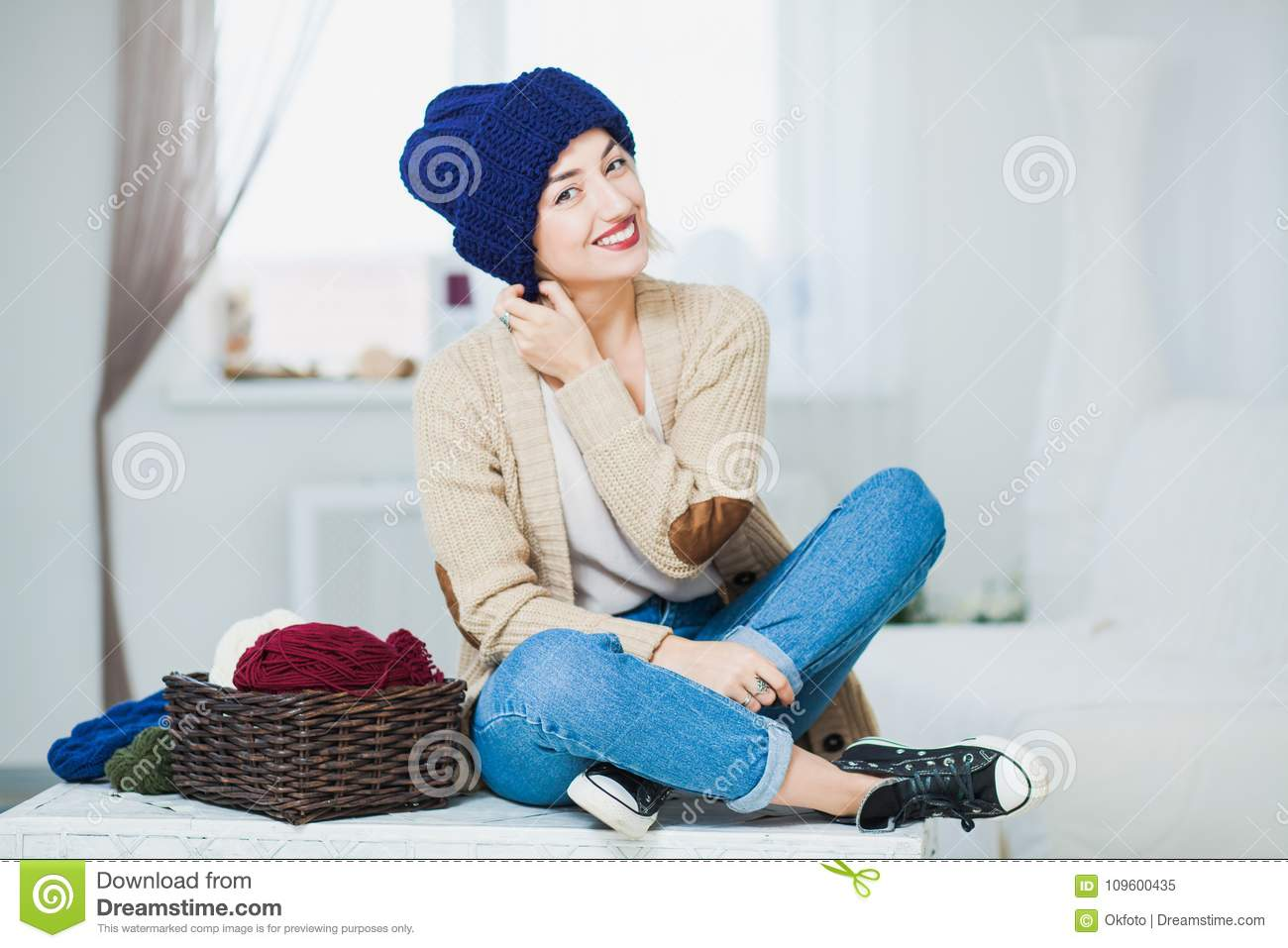 d35472edd1e Beautiful woman in big white knitted hat indoors sit on chest with basket  yarn. Knitting at home