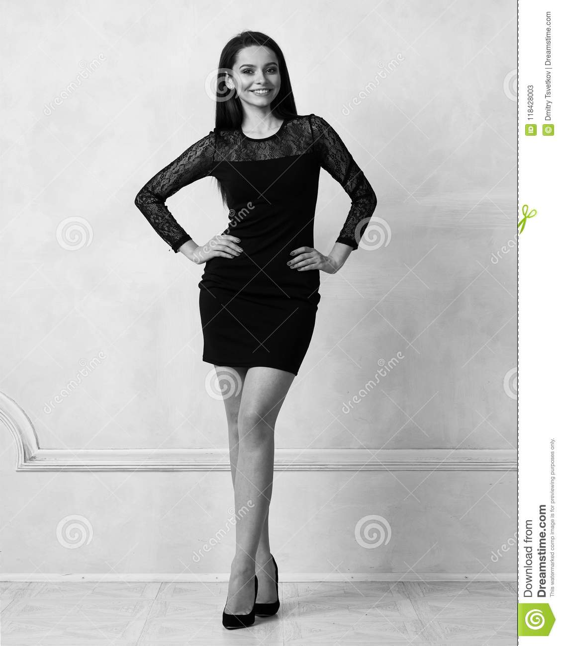 636fba24d25d Beautiful female model with long brunette hair demonstrating black bodycon  dress with straps and lace hem. Young attractive fashionable woman posing  in ...