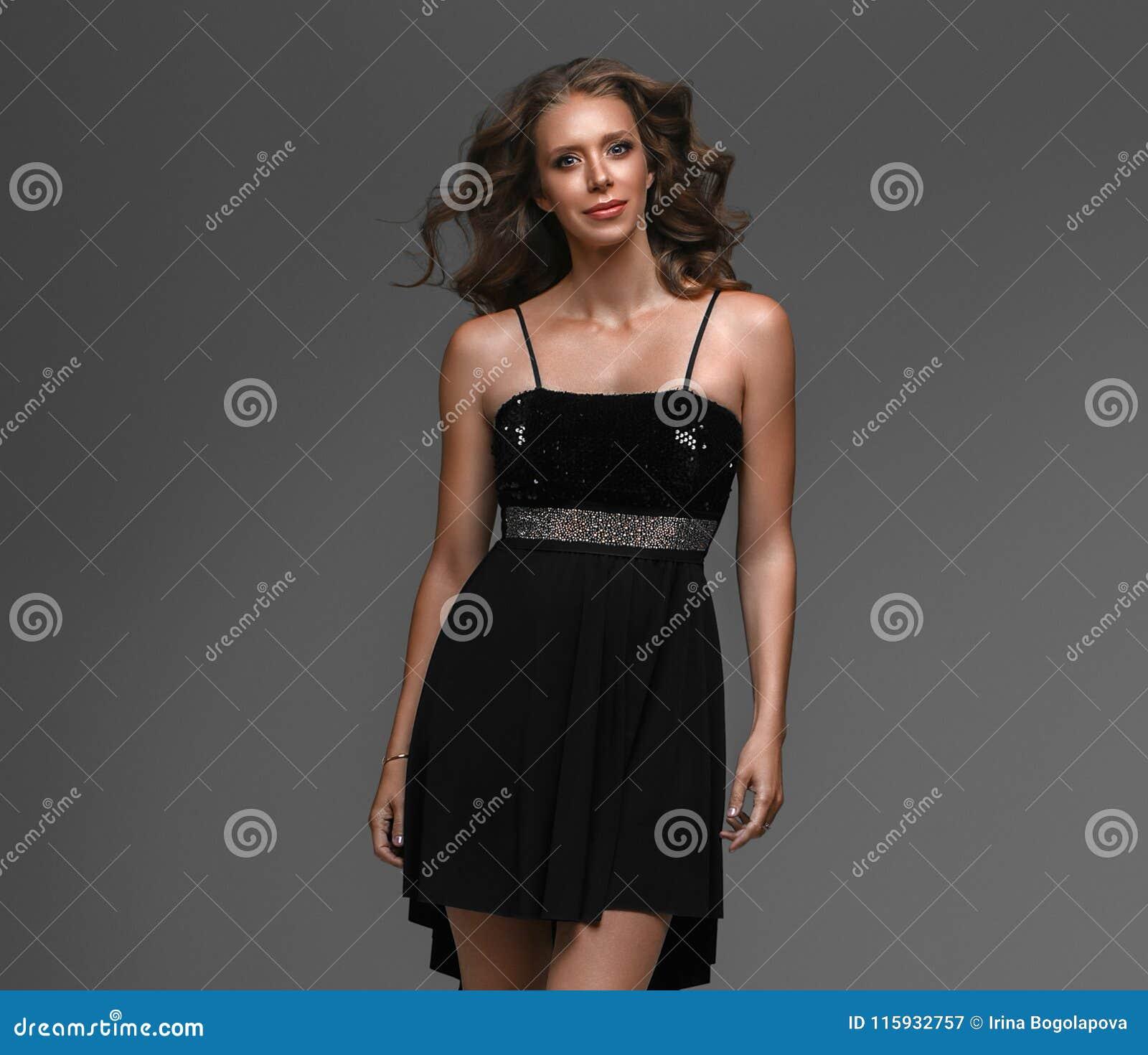 eec0a083f4 Beautiful woman in black dress elegant over gray background. Studio shot.