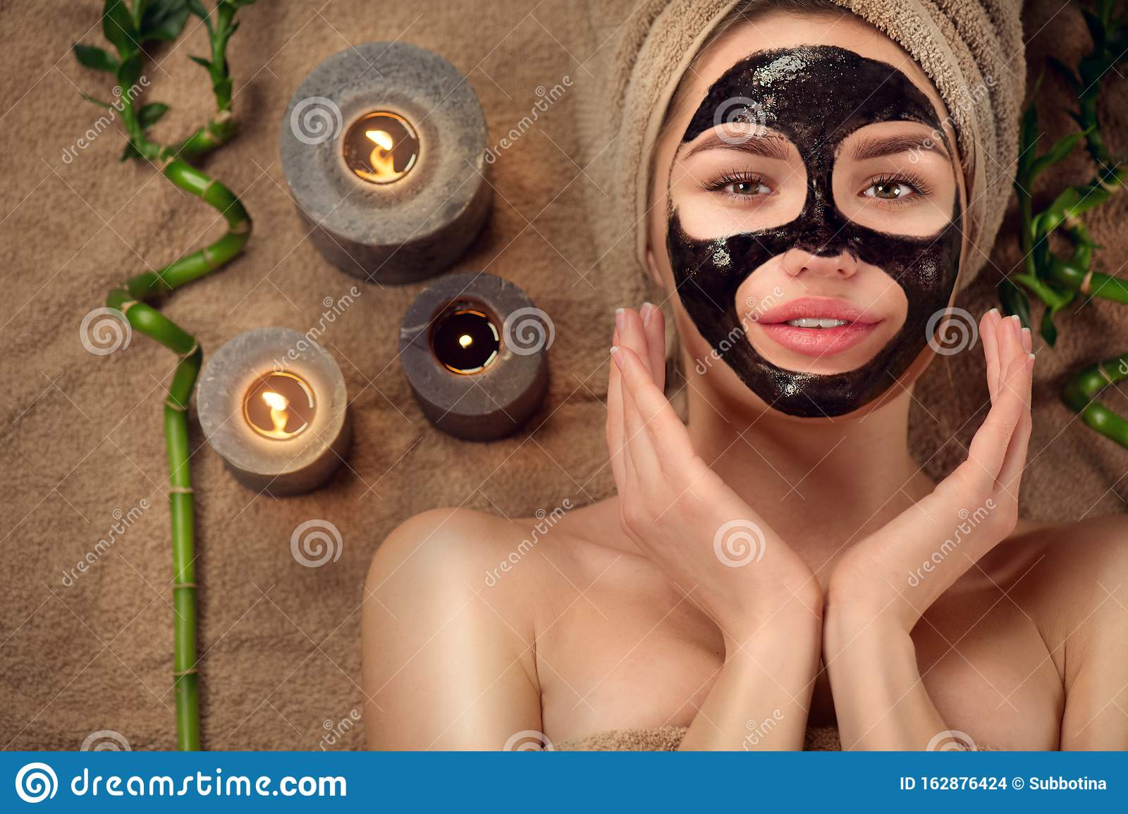 Beautiful woman with black purifying black charcoal mask on her face. Beauty model girl with black facial peel-off mask