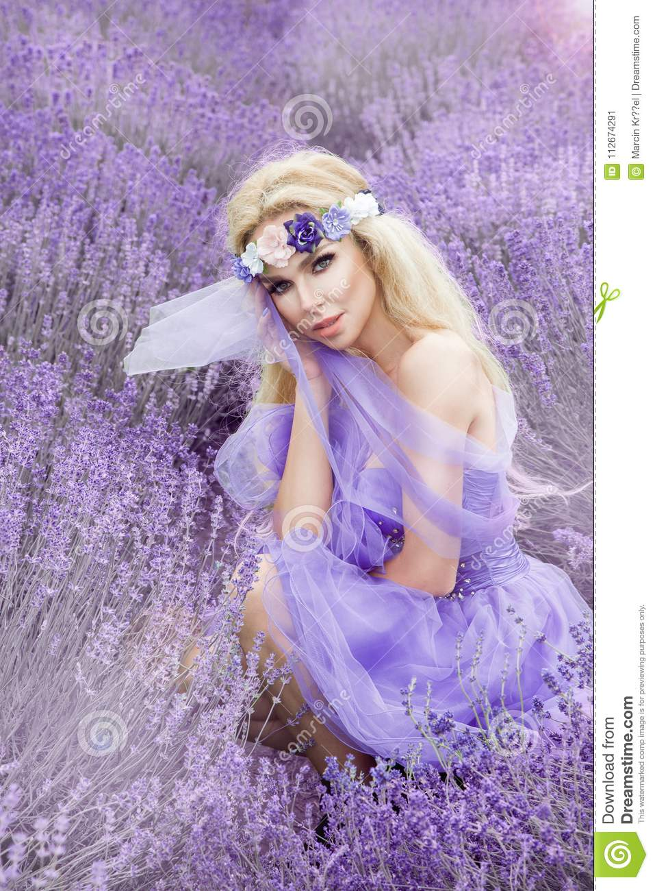 Beautiful woman with blond hair in a beautiful long white wedding beautiful woman with blond hair in a beautiful long white wedding dress stands on a field with heather flowers in purple mightylinksfo