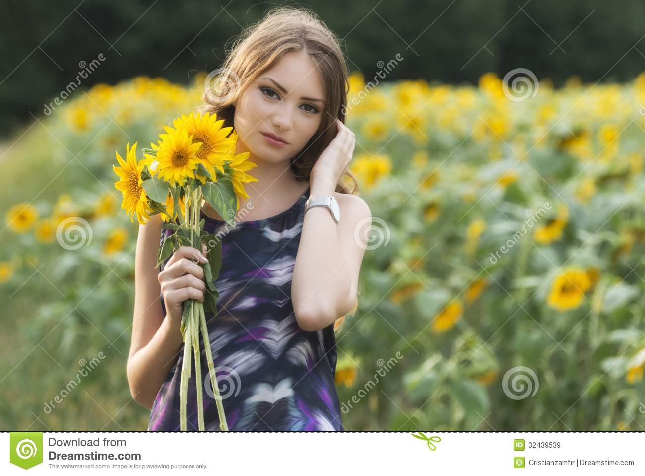 Beautiful woman on blooming sunflower field in summer