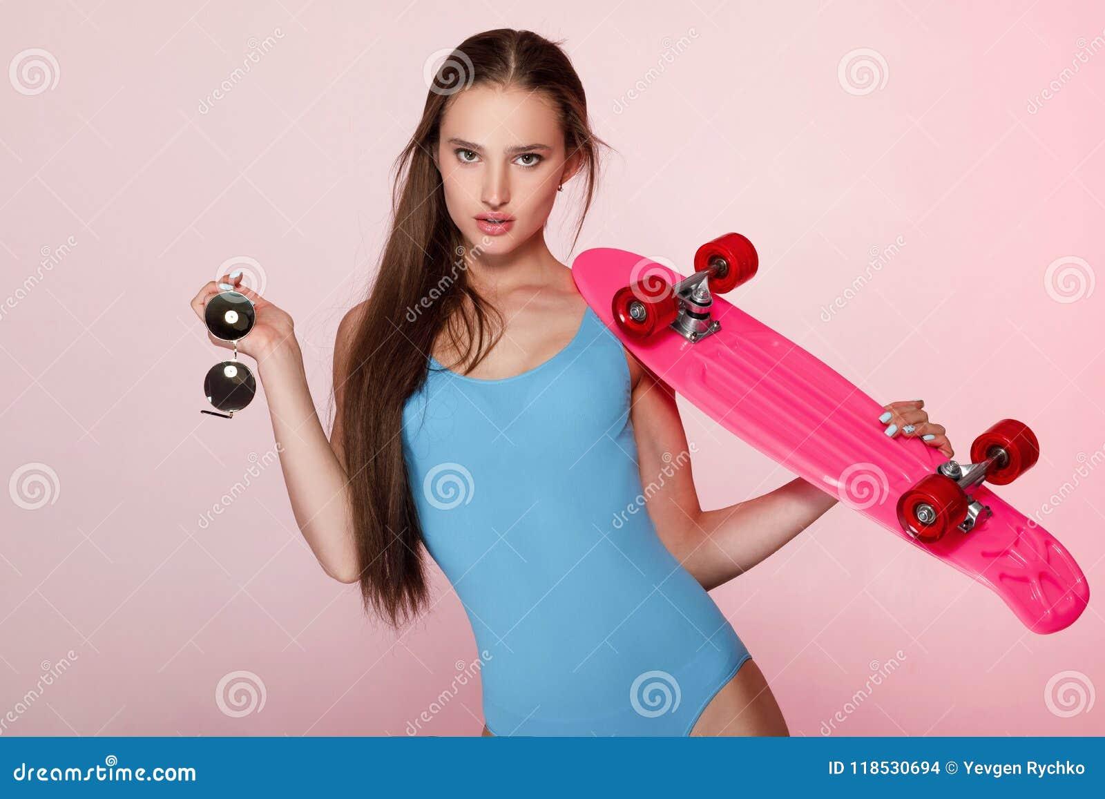 Beautiful woman holding skateboard