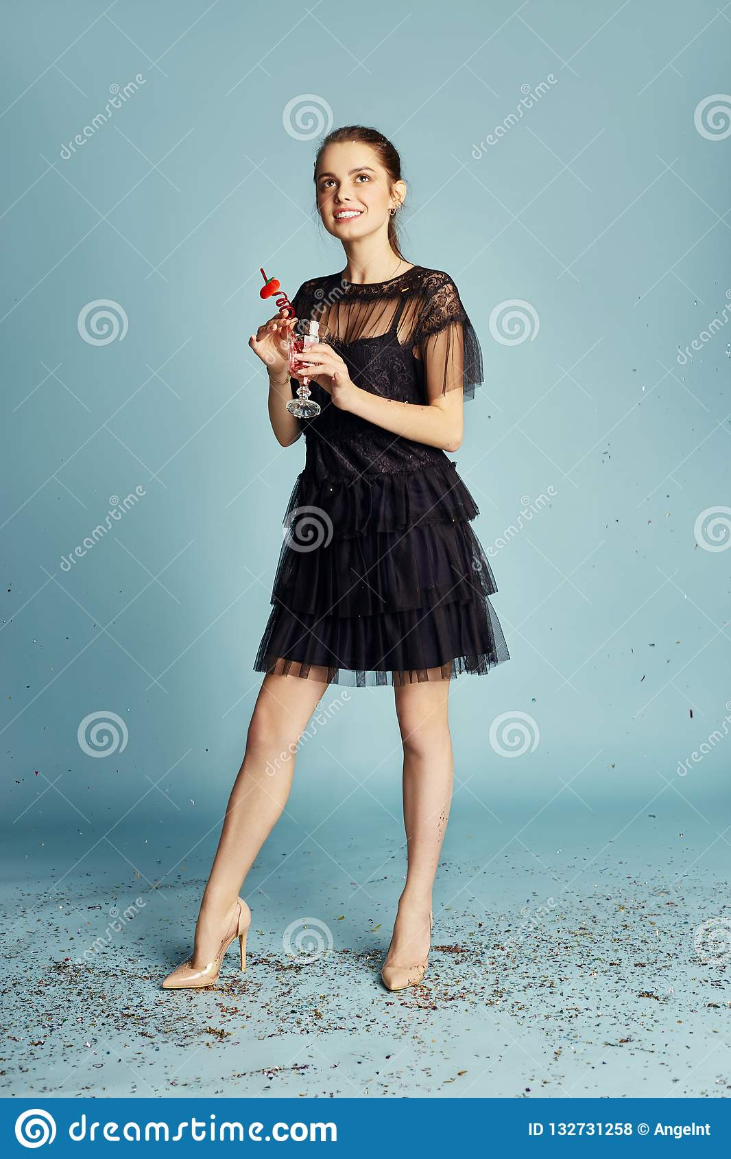 Beautiful Woman celebrating a birthday party having fun laughing and eating cakes under flying confetti. Girl posing and smiling