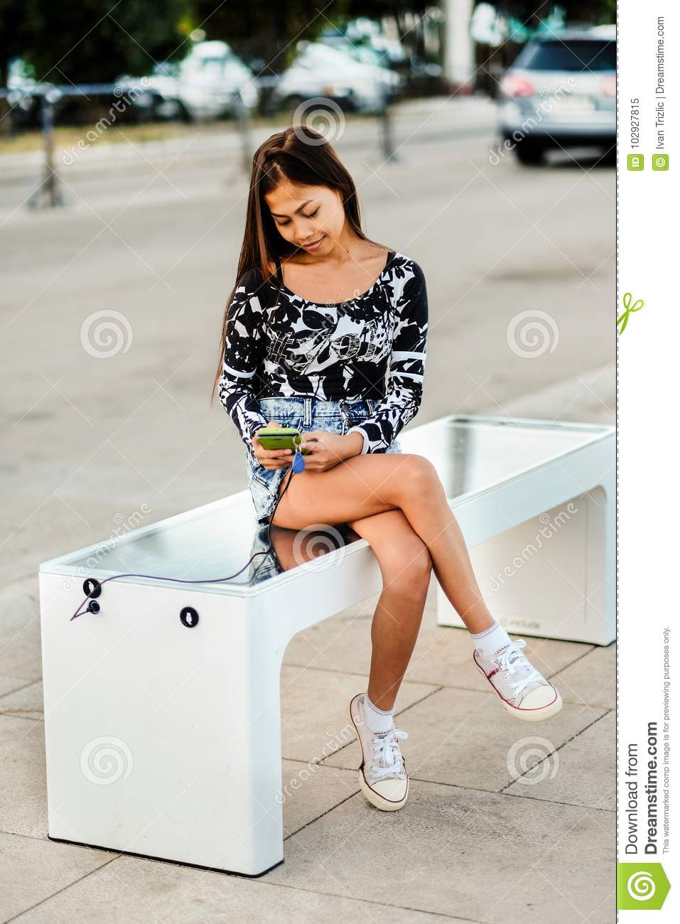 Beautiful woman charging her phone on free multipurpose solar panel charger incorporated in to sitting bench for citizens.Modern t