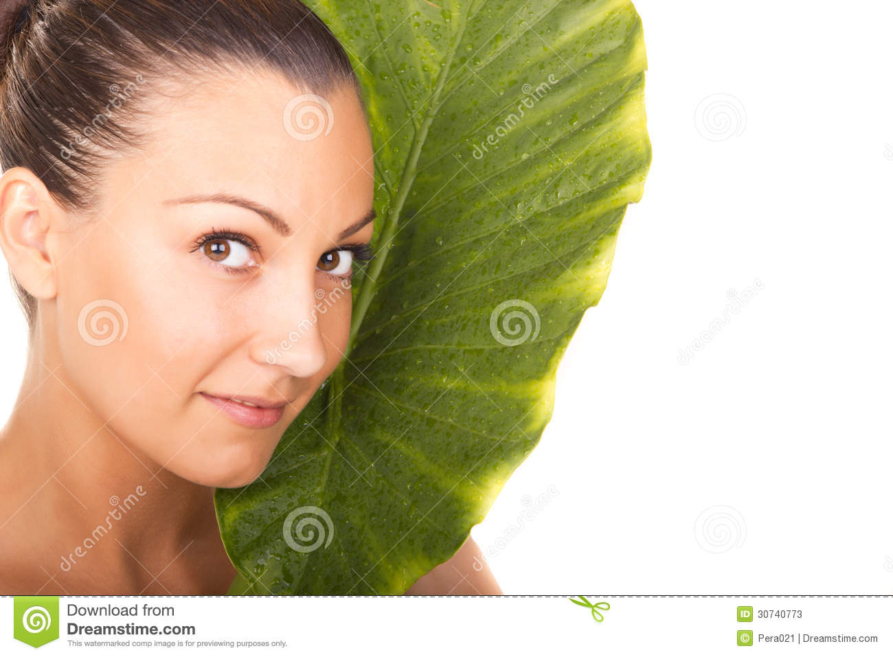 Beautiful woman closeup face portrait with green leaf
