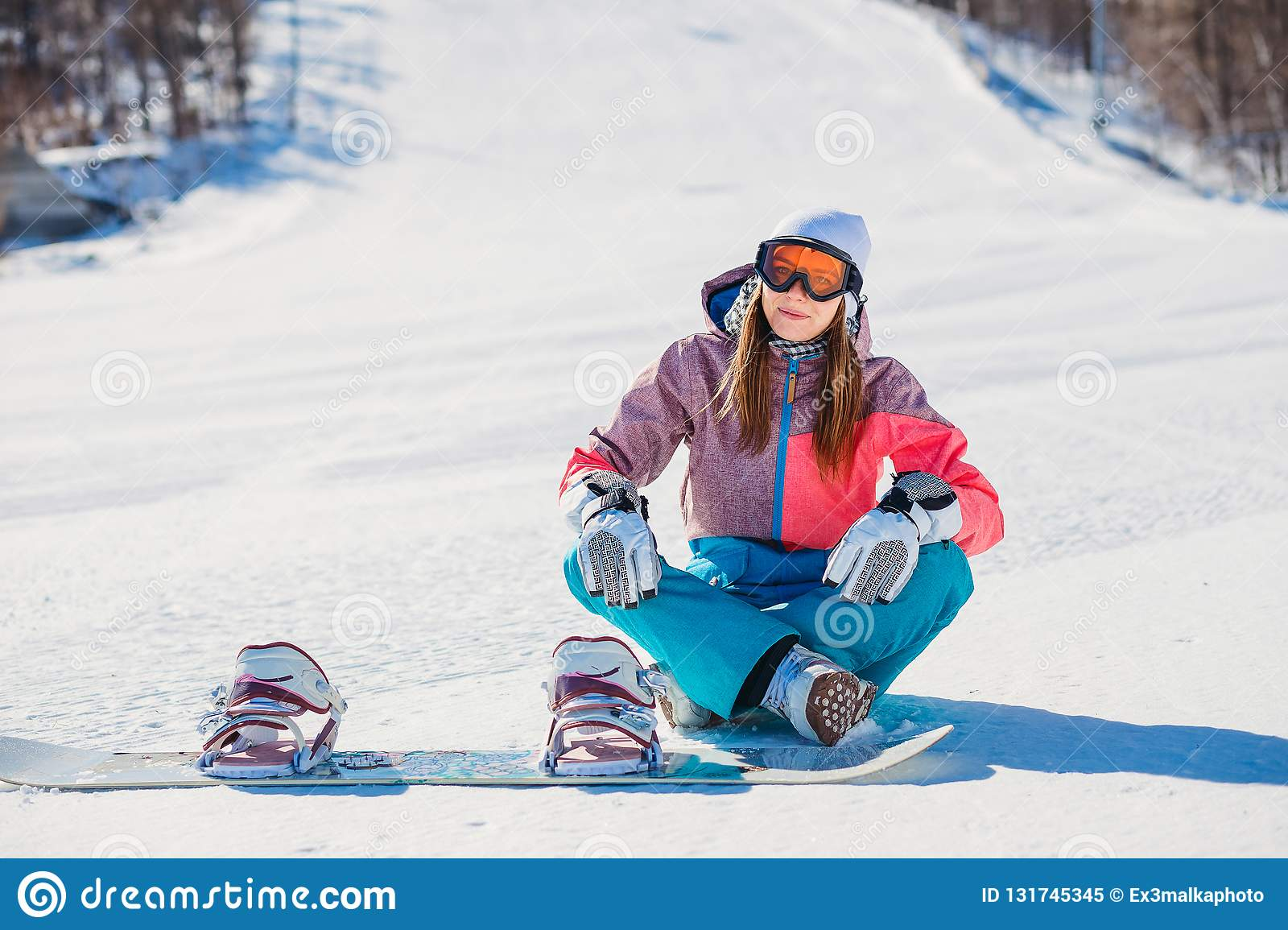 5c9e187a06 A Beautiful Woman In Clothing For Snowboarding Sitting On The Track ...