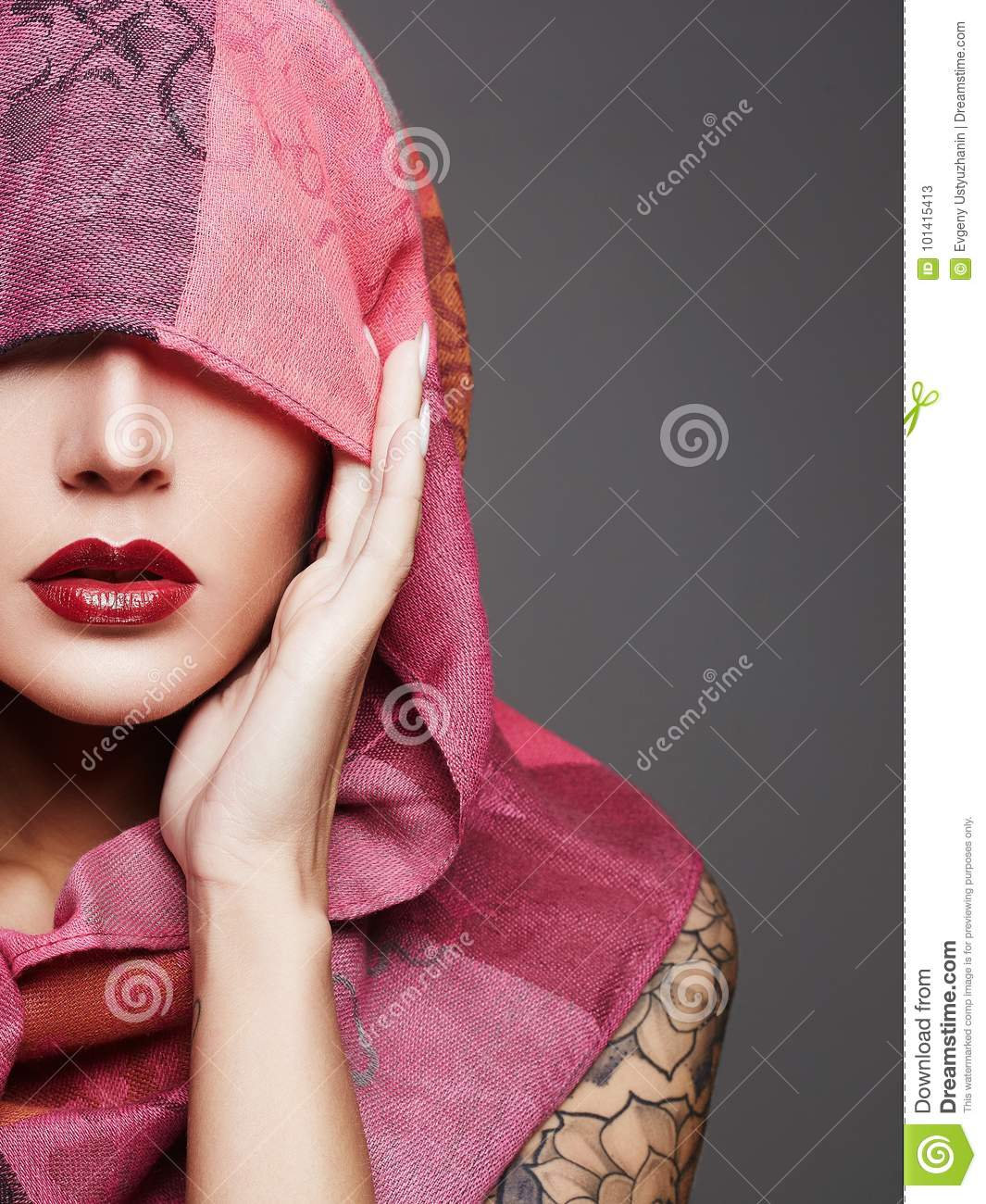 Beautiful woman covers her face with a colored hood.red lips make-up girl.  part of female face 407d789b4