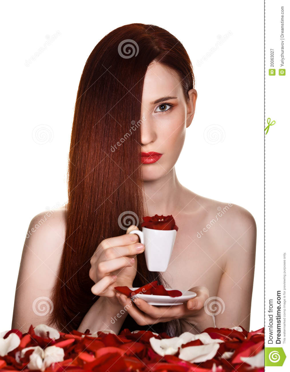 Beautiful woman and cup of rose petals