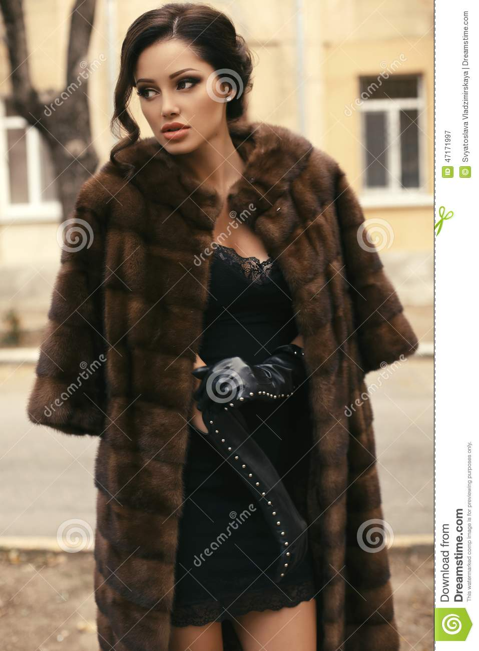 Beautiful woman with dark hair in luxurious fur coat and gloves