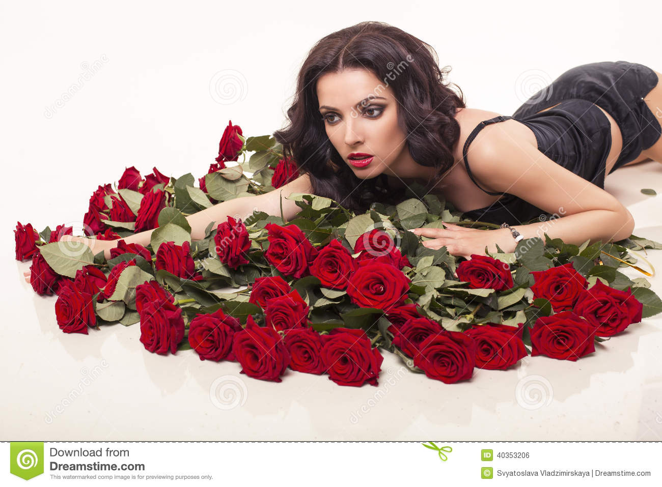7e471450c1 Beautiful woman with black hair in elegant lace dress posing with bouquet  of red roses
