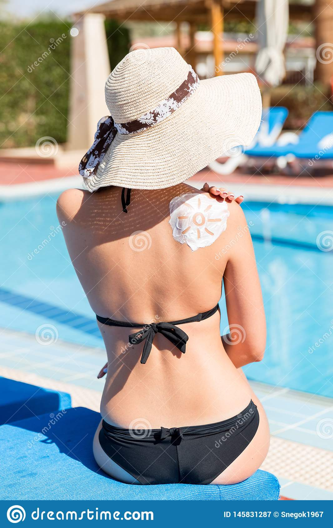 Beautiful woman with drawn sun by sun cream on her shoulder by the pool. Sun Protection Factor in vacation, concept