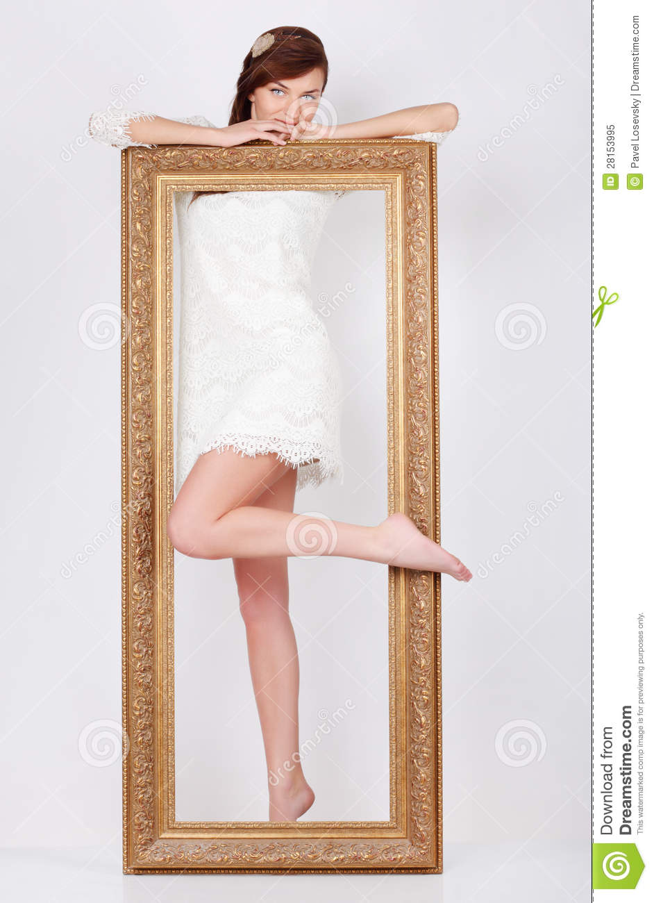 beautiful woman in dress stands behind big gilt frame