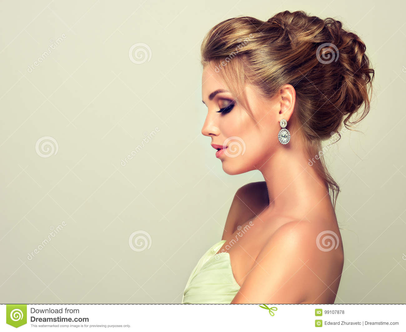 Young And Attractive Blond Model Dressed In Evening Gown And Jewelry