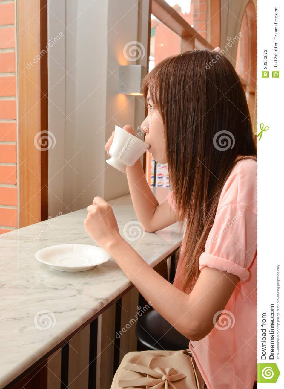 Beautiful woman drinking tea and looking out
