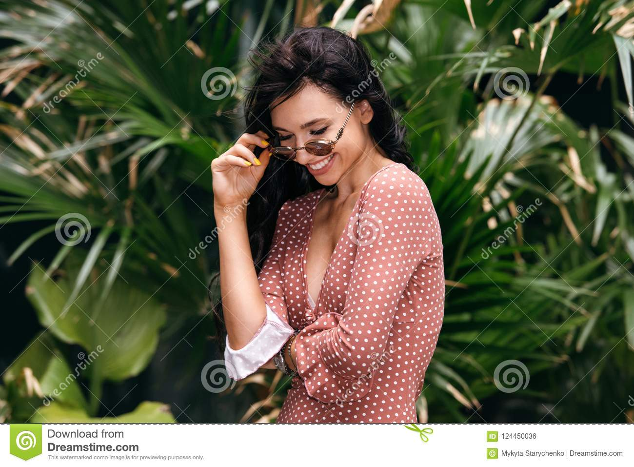 Beautiful woman enjoy travel lifestyle in tropical forest wearing sunglasses and summer dress.