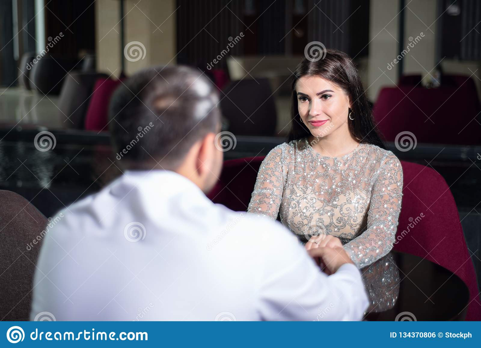 Beautiful woman in evening dress holding hands of man