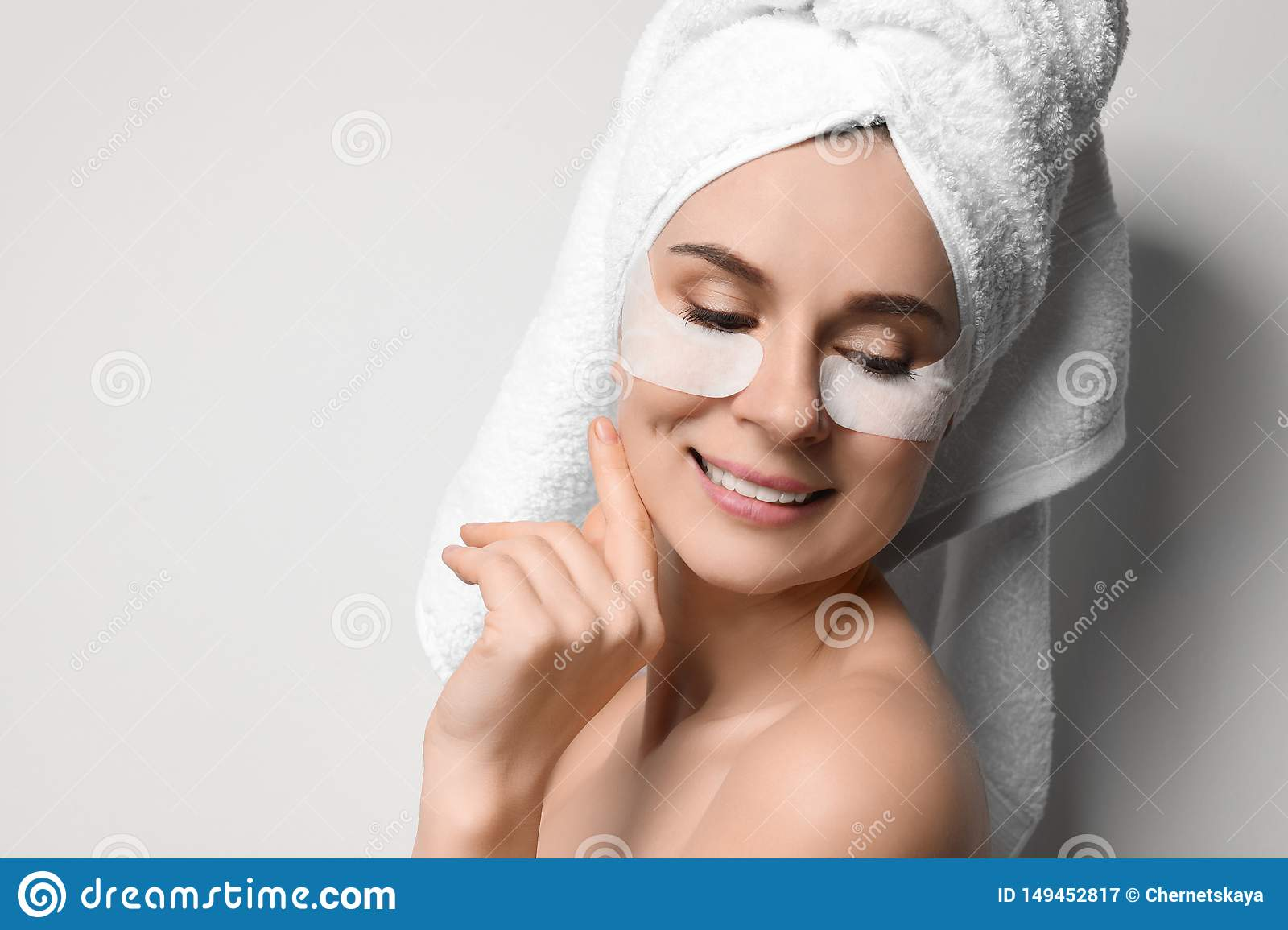 Beautiful woman with eye patches against light background