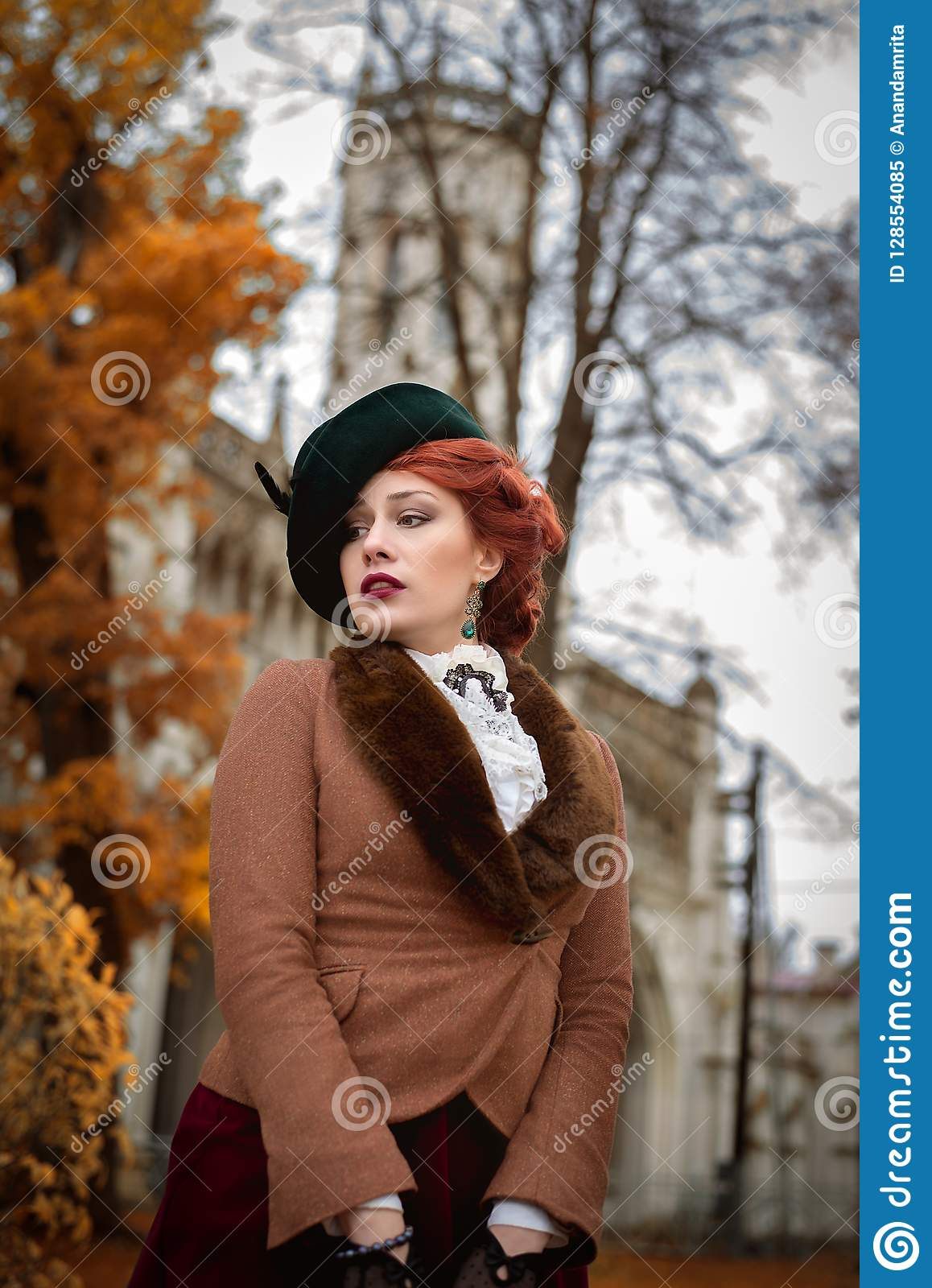 Beautiful woman face in the hat and red hair autumn trees