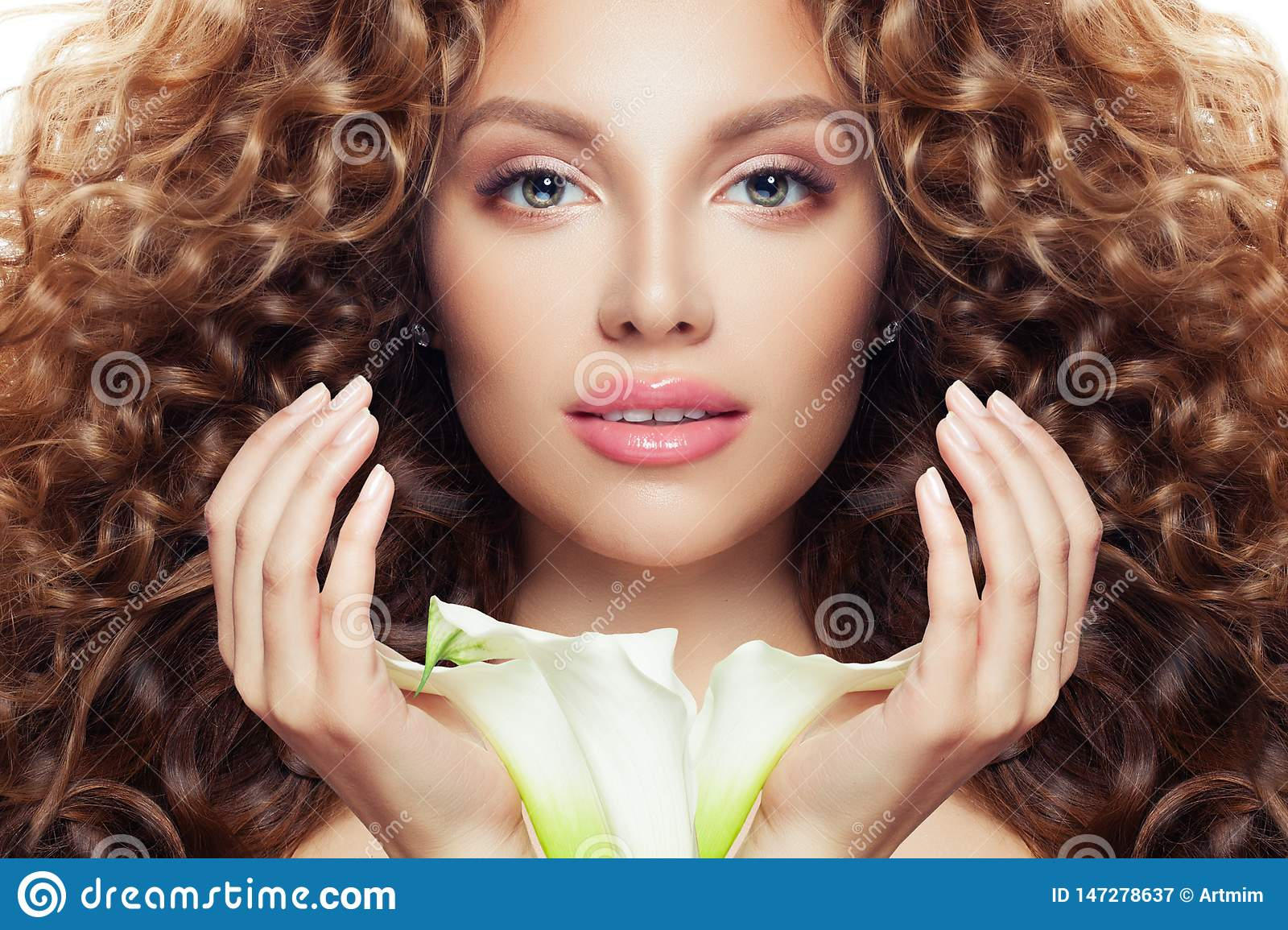 Beautiful woman face. Perfect model girl with long curly hair, clear skin and lily flower
